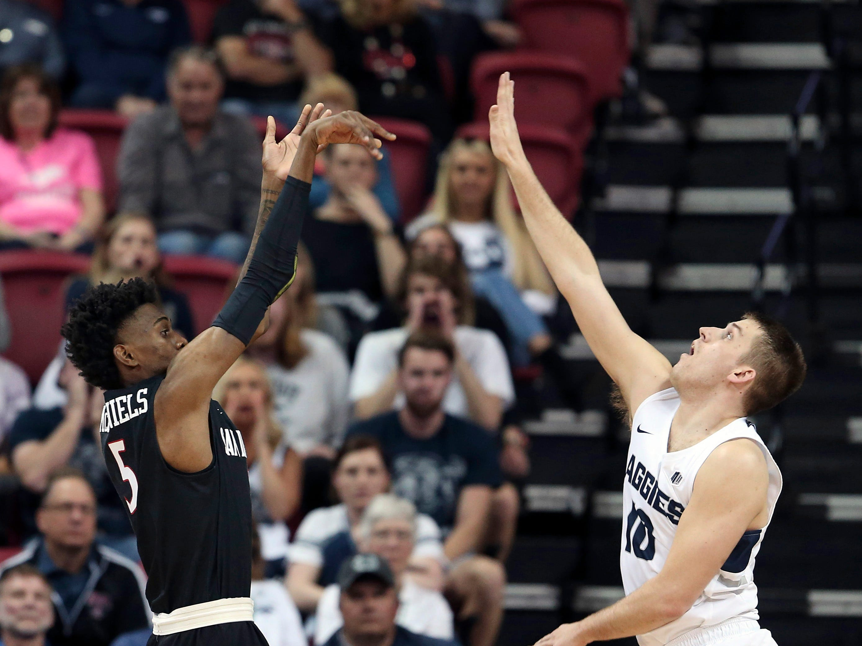 San Diego State's Jalen McDaniels shoots as Utah State's Quinn Taylor defends during the first half of an NCAA college basketball game in the Mountain West Conference men's tournament championship Saturday, March 16, 2019, in Las Vegas. \