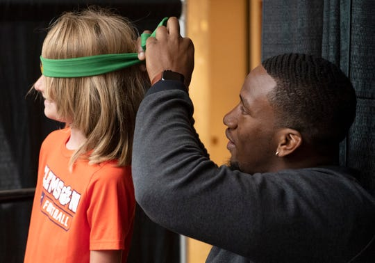 Former Clemson football player Clelin Ferrell ties a Power Rangers headband that he gave to Ben Lewis, 11, of Charleston during an autograph signing at Haywood Mall Saturday, Mar. 16, 2019.