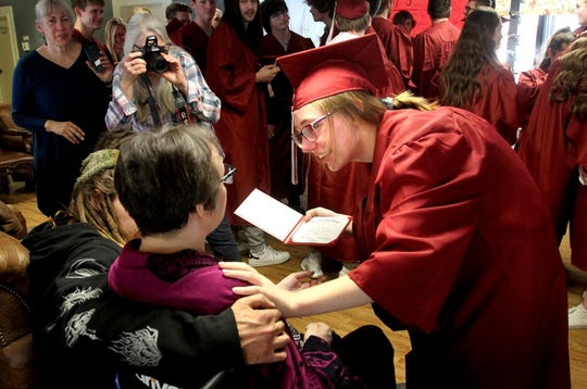 Hamilton High School senior Claire Matthews shows her mother, Susan Matthews, her high school diploma during a mock graduation at the Discovery Care Center in Hamilton, Mont., Wednesday, March 15, 2019. More than 30 fellow upperclassmen attended the event to support the Matthews family. (Perry Backus/The Ravalli Republic via AP)