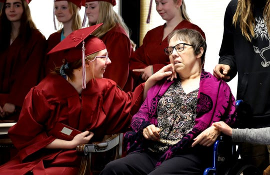With her diploma in hand, Claire Matthews smiles at her mother, Susan, during a mock graduation that was held Wednesday, March 15, 2019 at the Discovery Care Centre in Hamilton, Mont. More than 30 Hamilton High School seniors attended the event. (Perry Backus/The Ravalli Republic via AP)