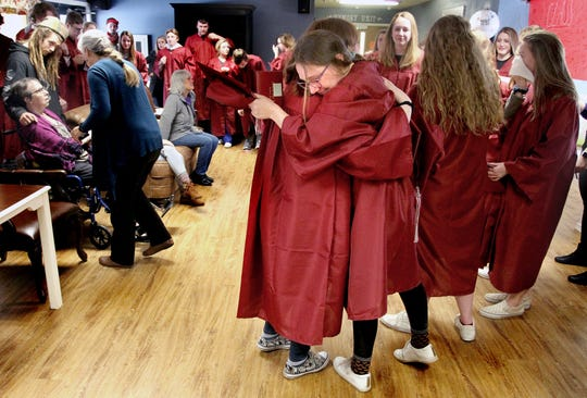 Hamilton High School senior Claire Matthews receives a hug from one of her fellow classmates during a mock graduation ceremony at the Discovery Care Center Wednesday, March 13, 2019. The ceremony offered Matthew's mother, Susan, the chance to see her daughter receive her high school diploma. Susan Matthews is currently in hospice care at the facility. (Perry Backus/The Ravalli Republic via AP)