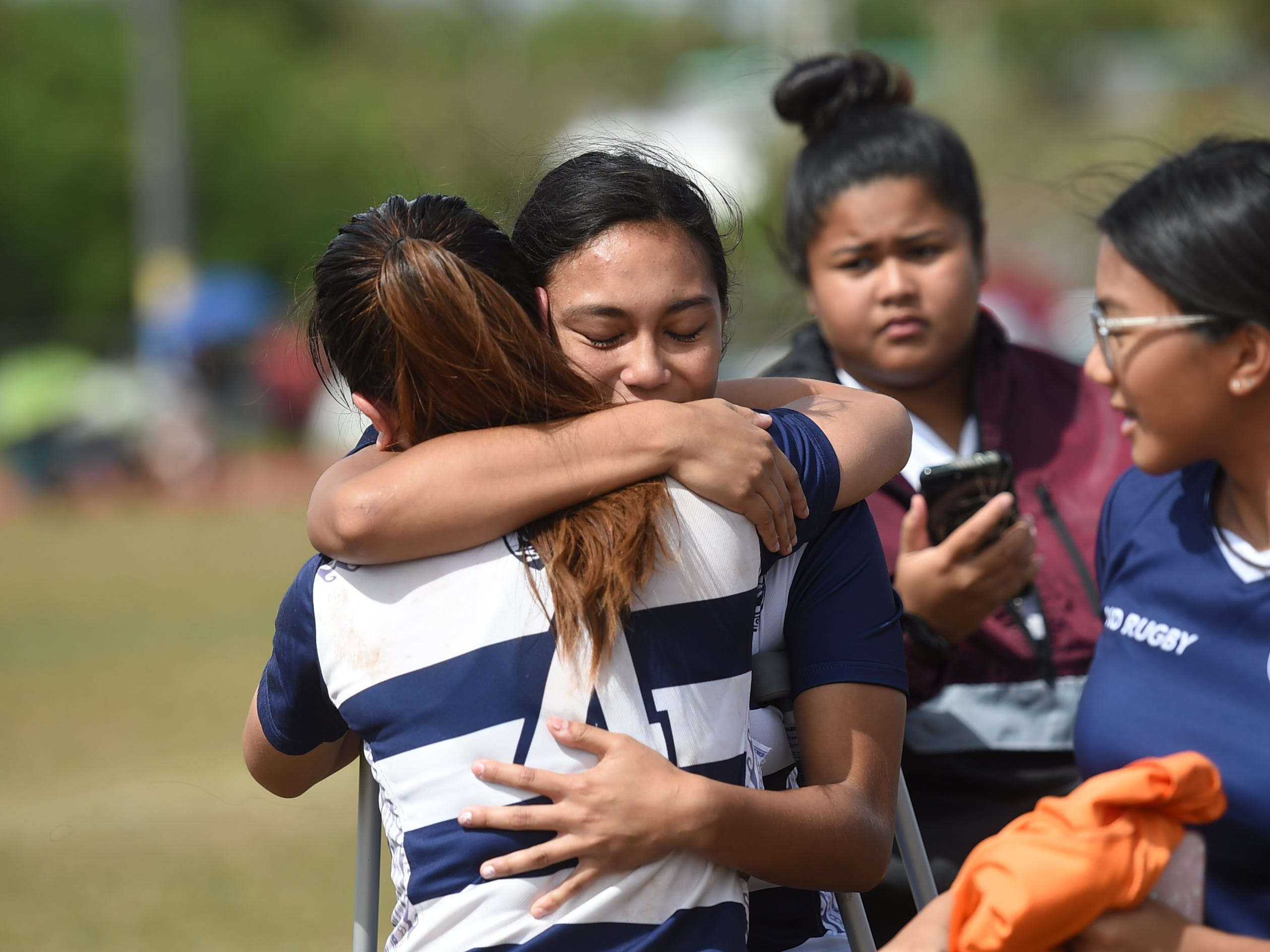 Notre Dame Royals players embrace following their their 21-17 win in the GRFU/IIAAG Girls Rugby Finals against the George Washington Geckos at the GW High School Field in Mangilao, March 16, 2019.