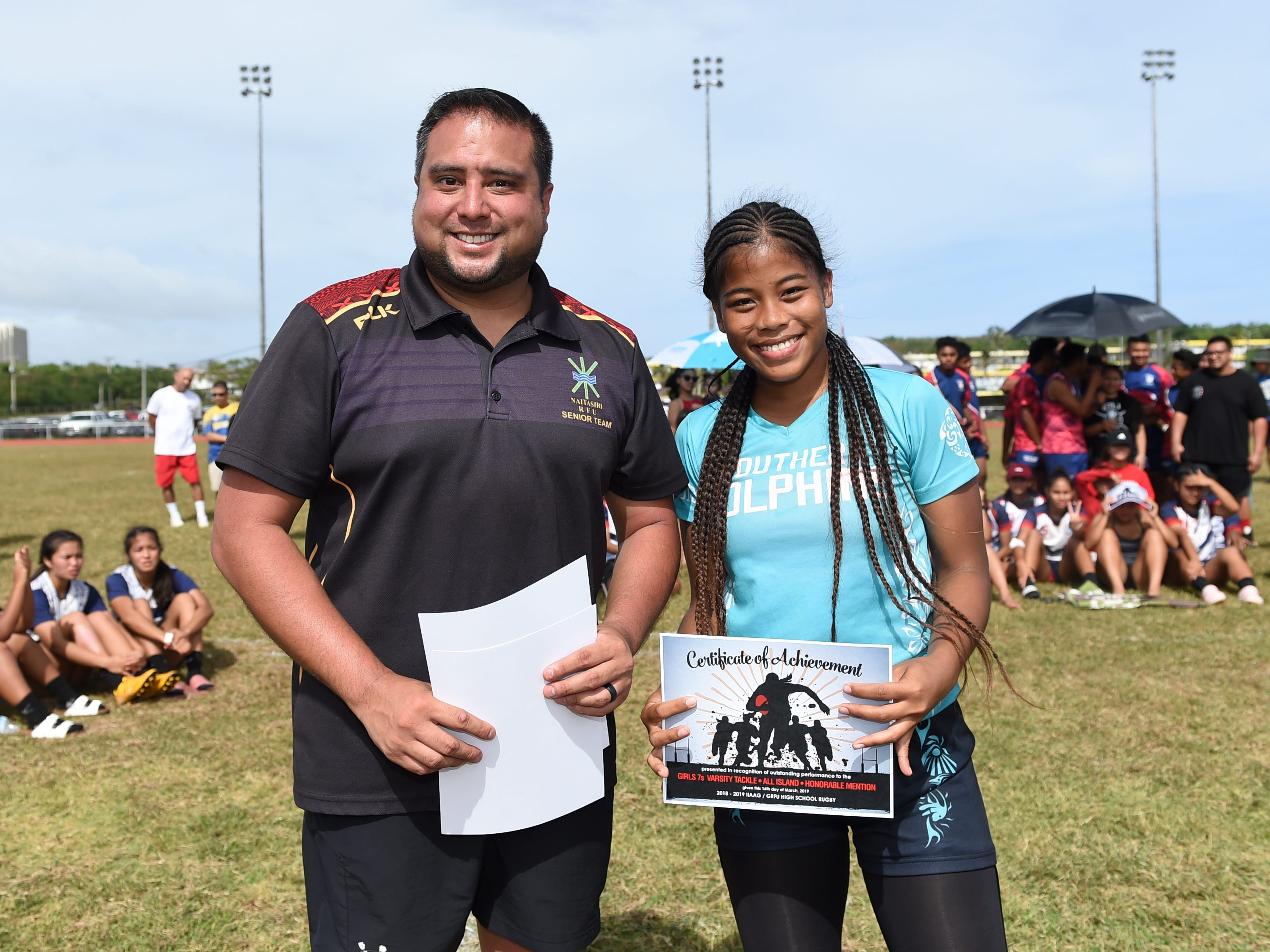 Southern High's Jayann Andrew receives a 2018-2019 IIAAG/GRFU Girls Rugby Honorable Mention award from Fernando Esteves, the league director, at the George Washington High School Field, March 16, 2019.