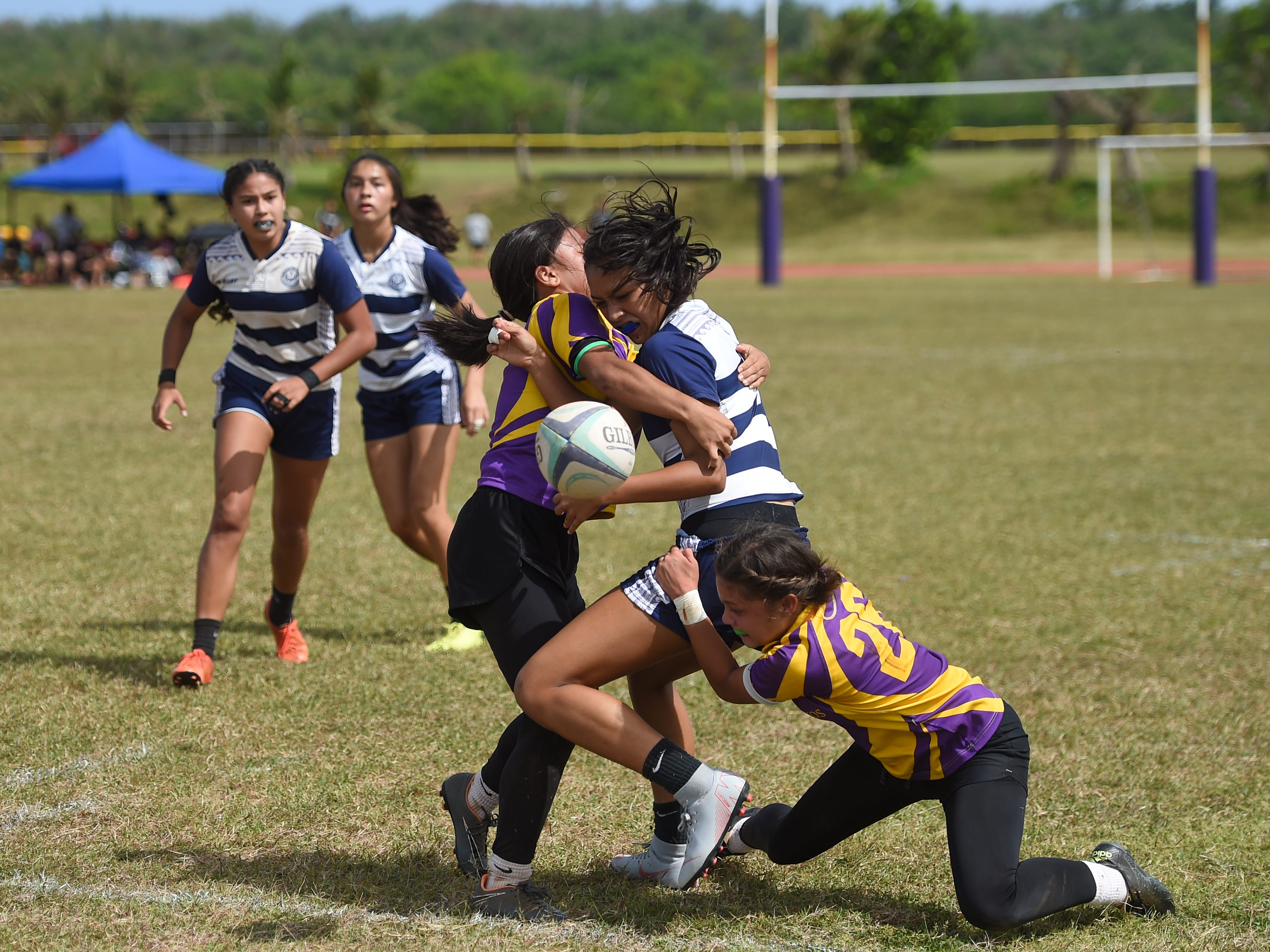 Notre Dame's Brianne Leon Guerrero is tackled by George Washington Geckos players during their GRFU/IIAAG Girls Rugby Finals game at the GW High School Field in Mangilao, March 16, 2019. The Royals went on to beat the Geckos 21-17 for the rugby title.