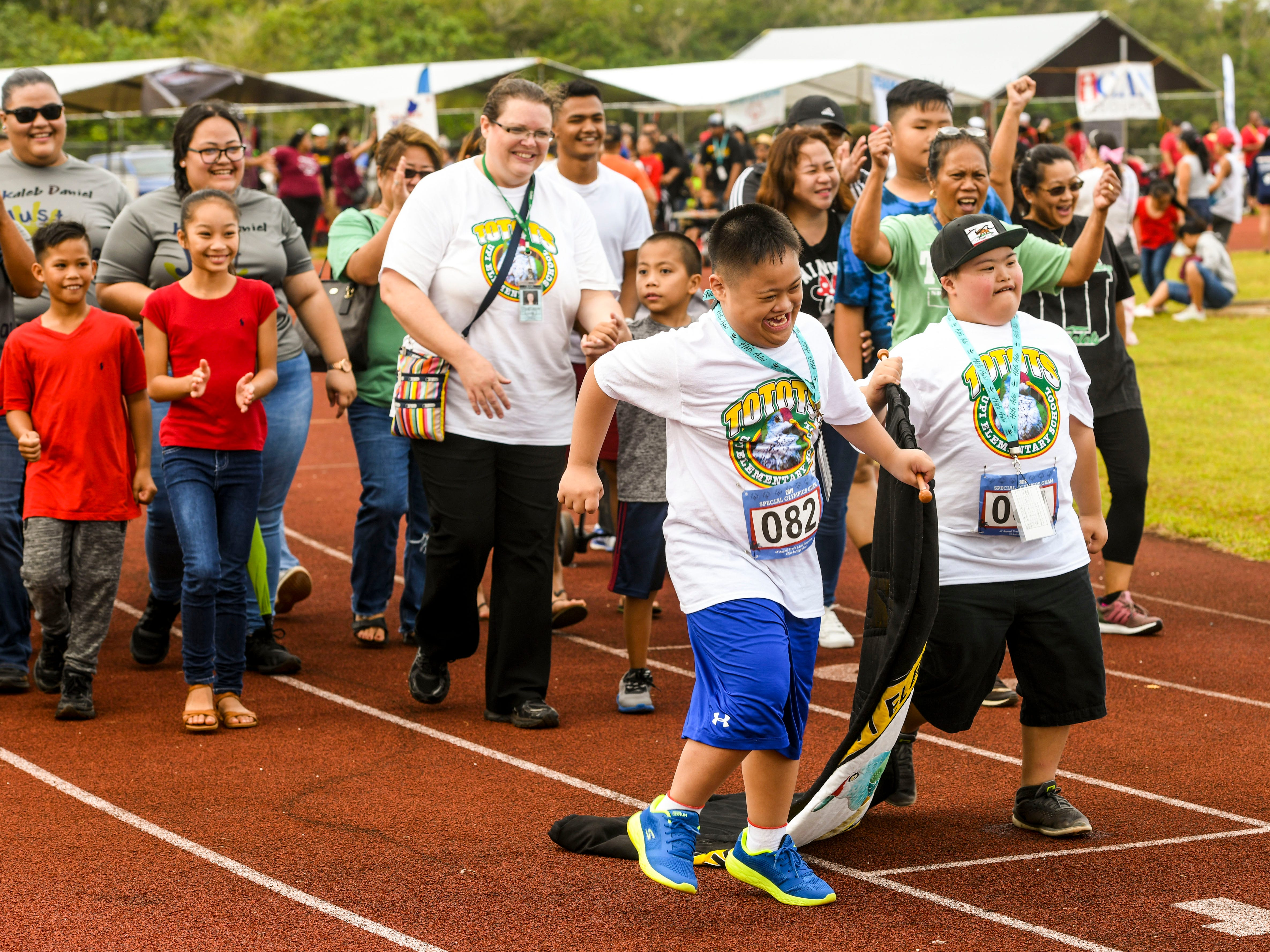 Special Olympians Jacob Palad, front left, and Kaleb Cruz give a little celebration dance as they serve as banner carriers for the Upi Elementary School delegation during the 43rd Special Olympics Guam Track & Field competition at Okkodo High School in Dededo on Saturday, March 16, 2019.