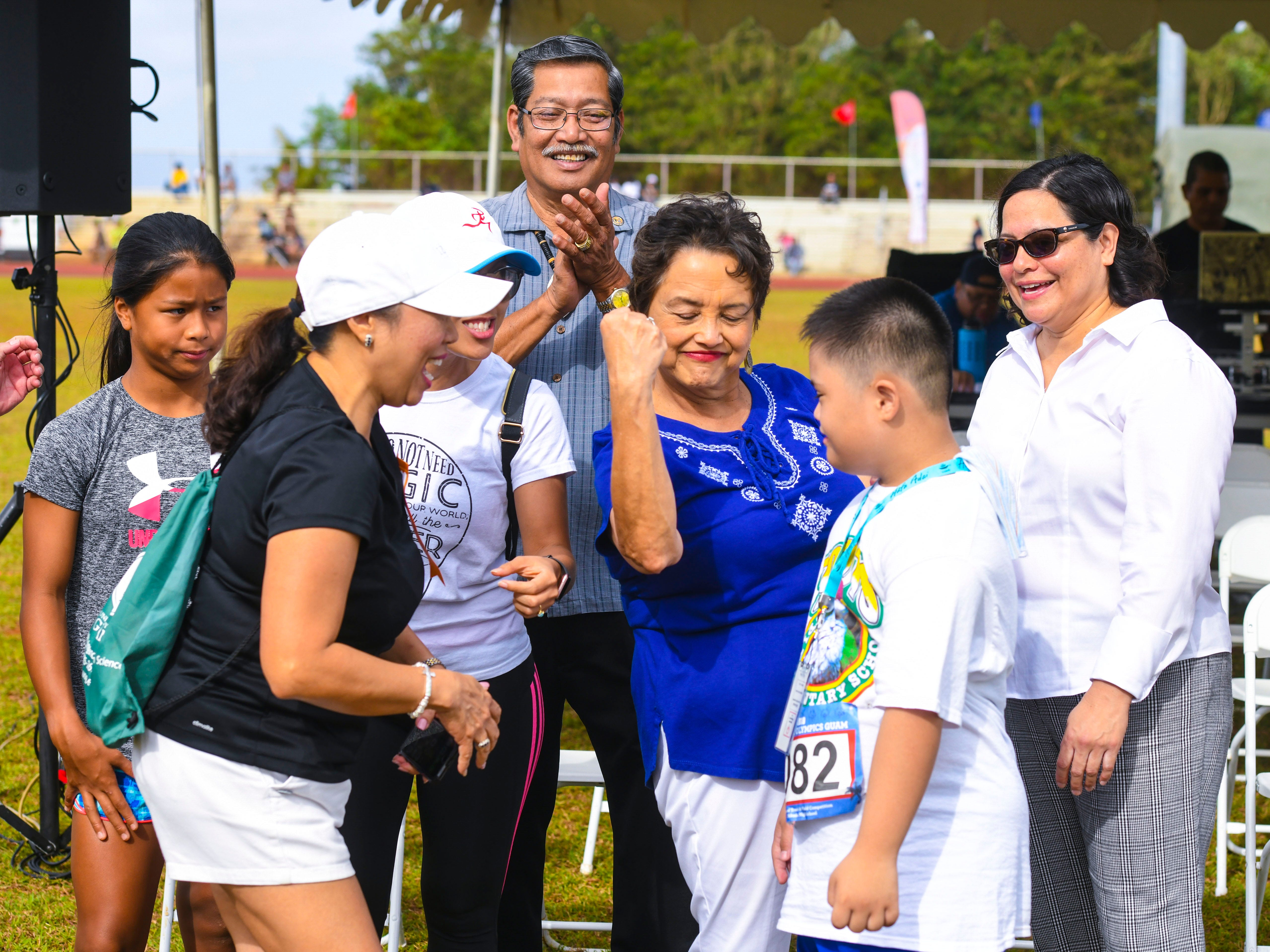 """Gov. Lou Leon Guerrero display her """"guns"""" to motivate Special Olympian Jacob Palad during the 43rd Special Olympics Guam Track & Field competition at Okkodo High School in Dededo on Saturday, March 16, 2019."""
