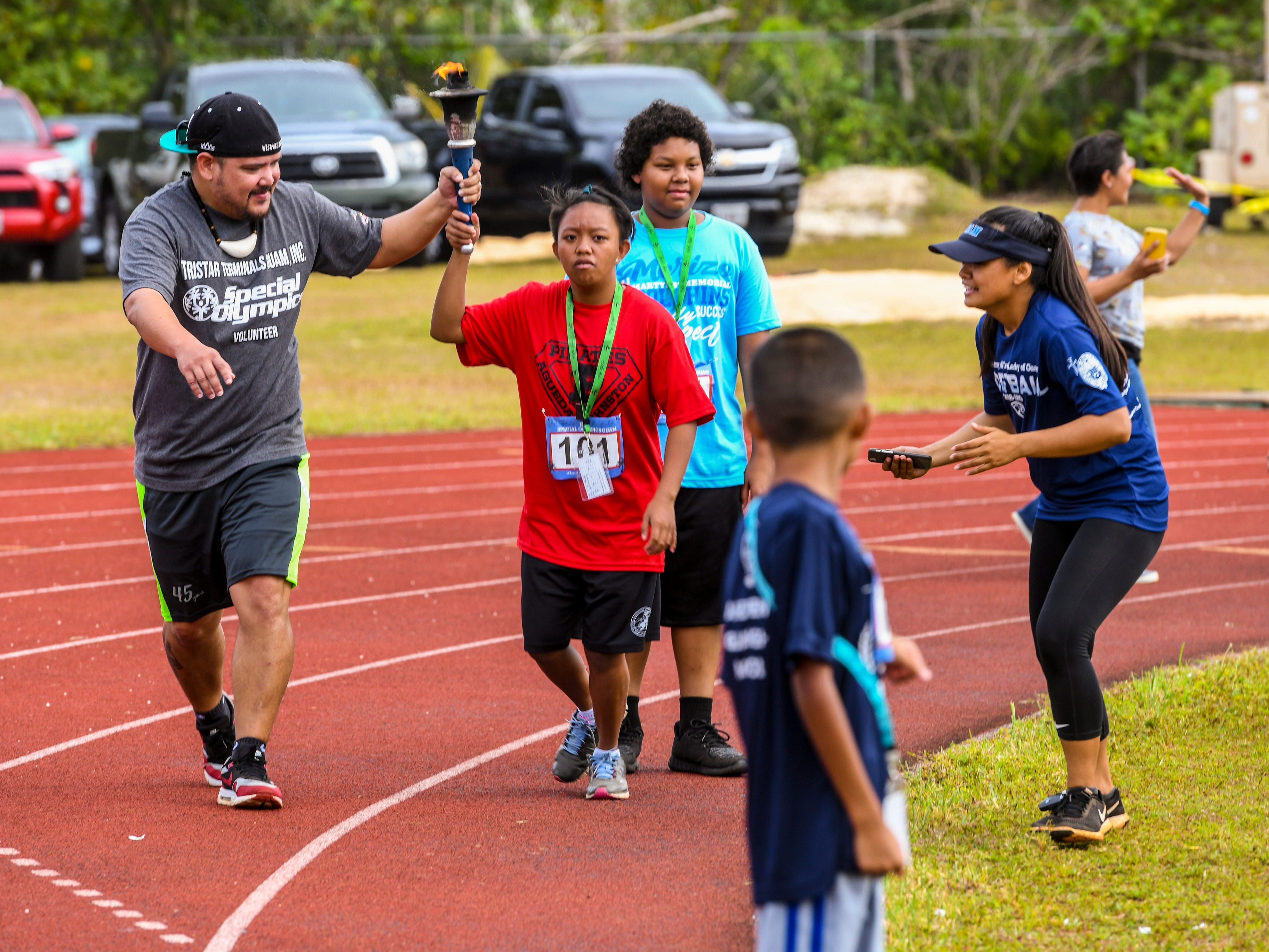 Special Olympian Angel Obra (101) carries the flame through her section of the track during the torch relay at the 43rd Special Olympics Guam Track & Field competition at Okkodo High School in Dededo on Saturday, March 16, 2019.