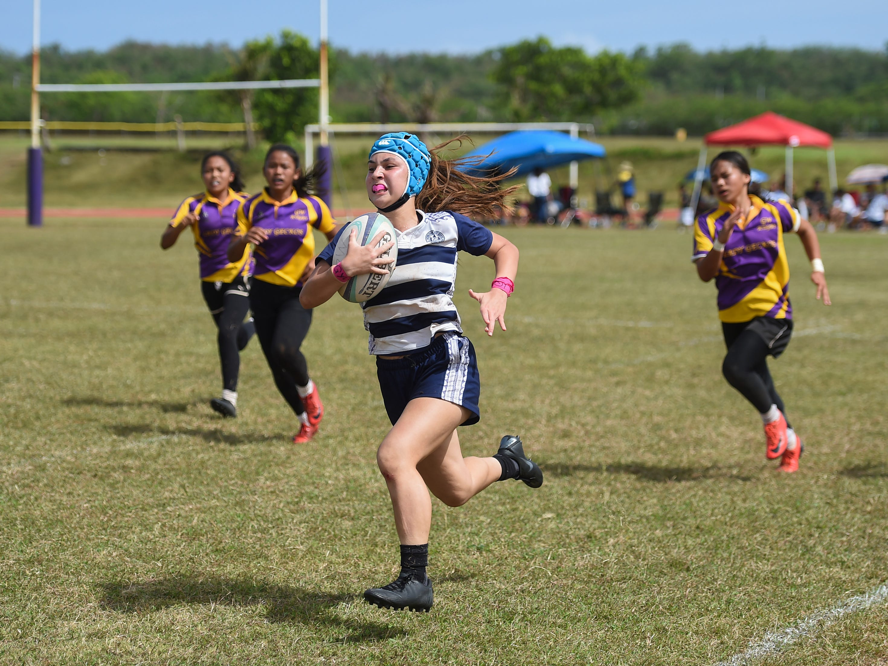 Notre Dame's Faith Moylan sprints down the sideline against the George Washington Geckos during their GRFU/IIAAG Girls Rugby Finals game at the GW High School Field in Mangilao, March 16, 2019. The Royals went on to beat the Geckos 21-17 for the rugby title.