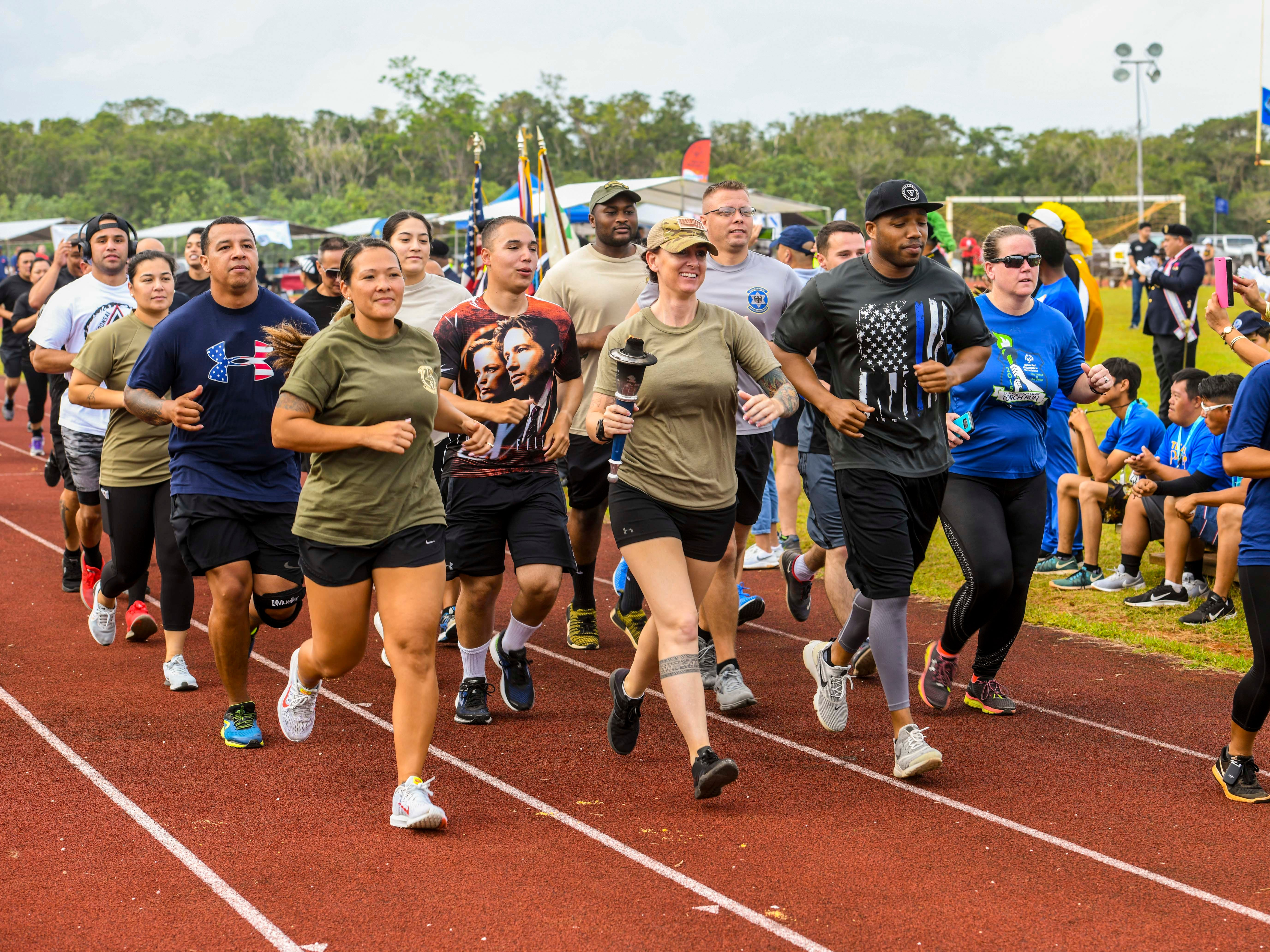Torch relay carriers gather together for a lap around the track before passing the flame to Special Olympians for their relay lap during the 43rd Special Olympics Guam Track & Field competition at Okkodo High School in Dededo on Saturday, March 16, 2019. Runners, from the local and military sectors, joined forces as they passed the flame in a relay fashion starting at the entrance of Naval Base Guam and proceeded to the Okkodo High School for the event.