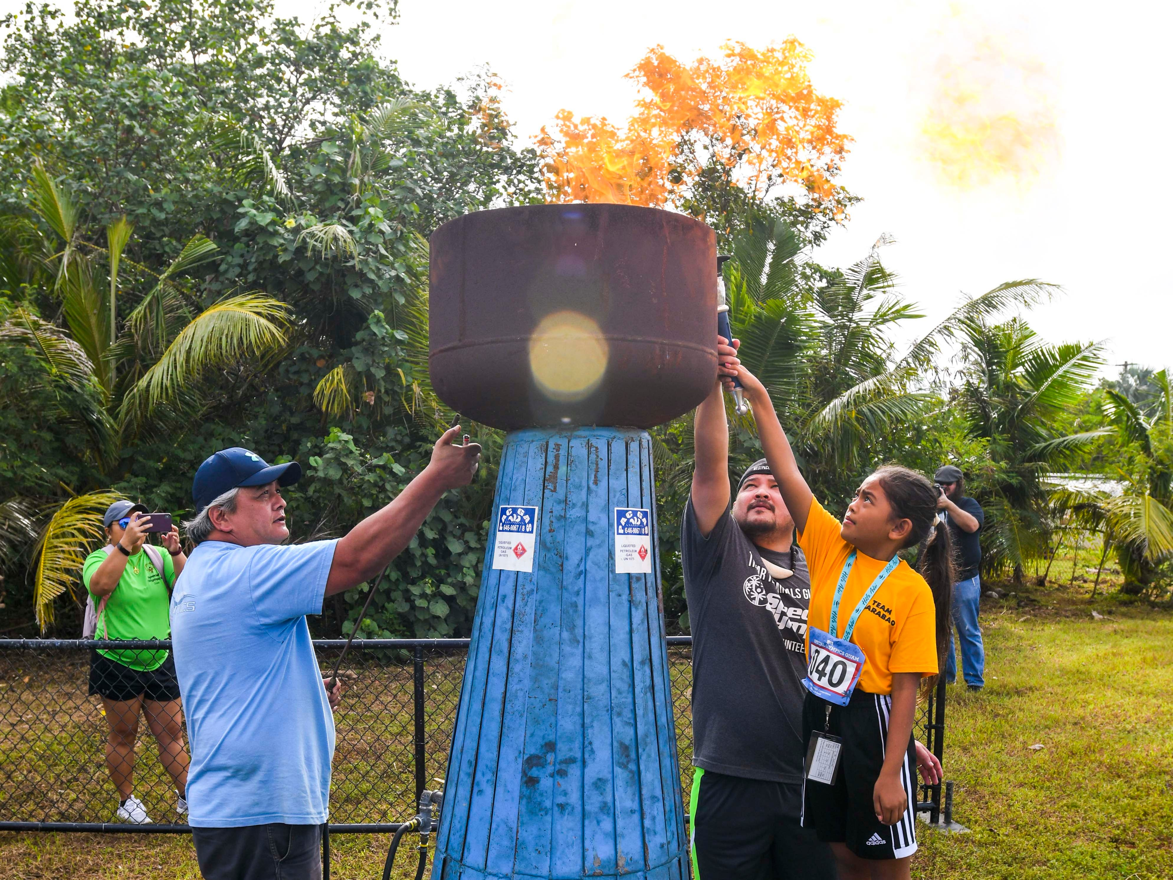 Special Olympian Zoey Lucero, right, ignites the main torch during the opening ceremony at the 43rd Special Olympics Guam Track & Field competition at Okkodo High School in Dededo on Saturday, March 16, 2019.