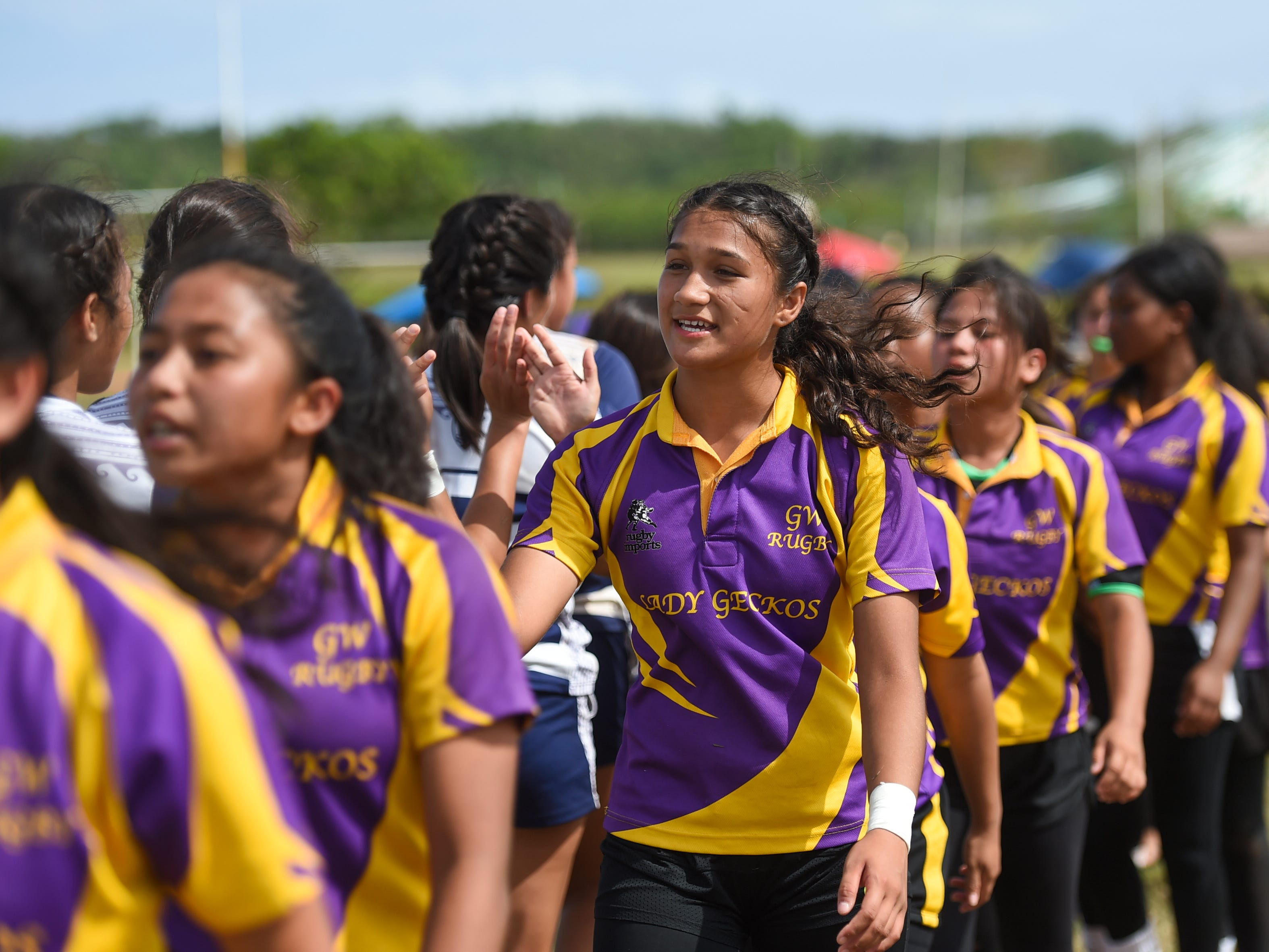 The Notre Dame Royals and George Washington Geckos shake hands following their GRFU/IIAAG Girls Rugby Finals game at the GW High School Field in Mangilao, March 16, 2019.