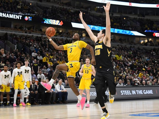 Zavier Simpson shoots for two over Iowa's Ryan Kriener in a 74-53 rout of the Hawkeyes.