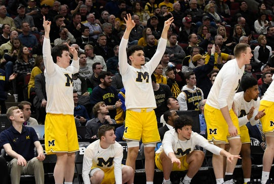 The Michigan Wolverines bench celebrates after a basket Friday in Chicago.