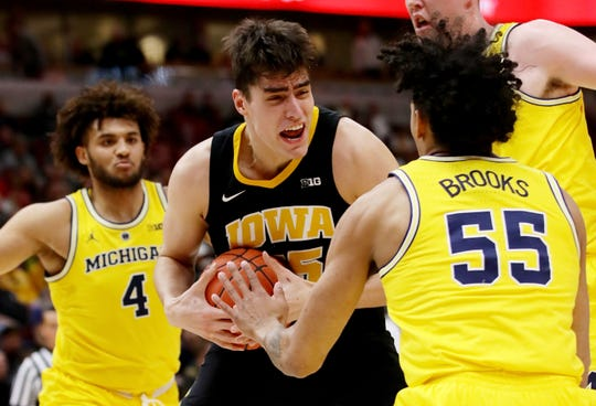 Iowa's Luke Garza dribbles the ball while being guarded by Michigan's Eli Brooks in the first half during the quarterfinals of the Big Ten tournament at the United Center on Friday, March 15, 2019 in Chicago, Illinois.