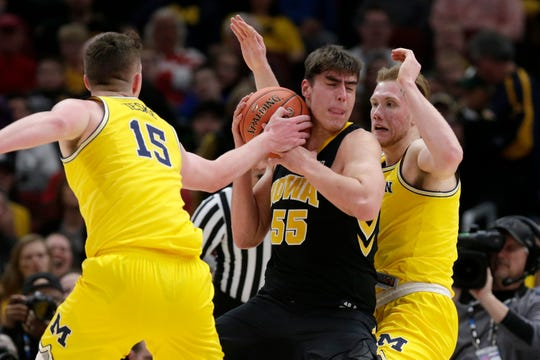 Iowa's Luka Garza (55) battles for the possession of the ball against Michigan's Jon Teske (15) during the first half of an NCAA college basketball game in the quarterfinals of the Big Ten Conference tournament, Friday, March 15, 2019, in Chicago. (AP Photo/Kiichiro Sato)