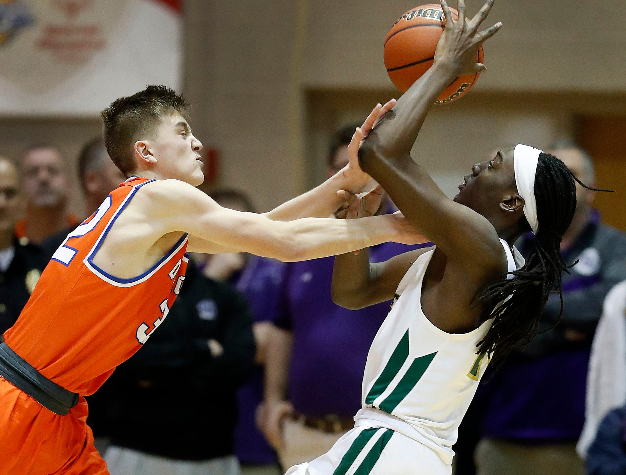 Crispus Attucks Tigers Jaiquan Edwards (23) is fouled by Silver Creek Dragons Kooper Jacobi (32) in the second half of their IHSAA boys' Semi-State basketball game at Seymour High School gym in Seymour IN, on Saturday, Mar. 16, 2019. The Silver Creek Dragons defeated the Crispus Attucks Tigers 72-69.