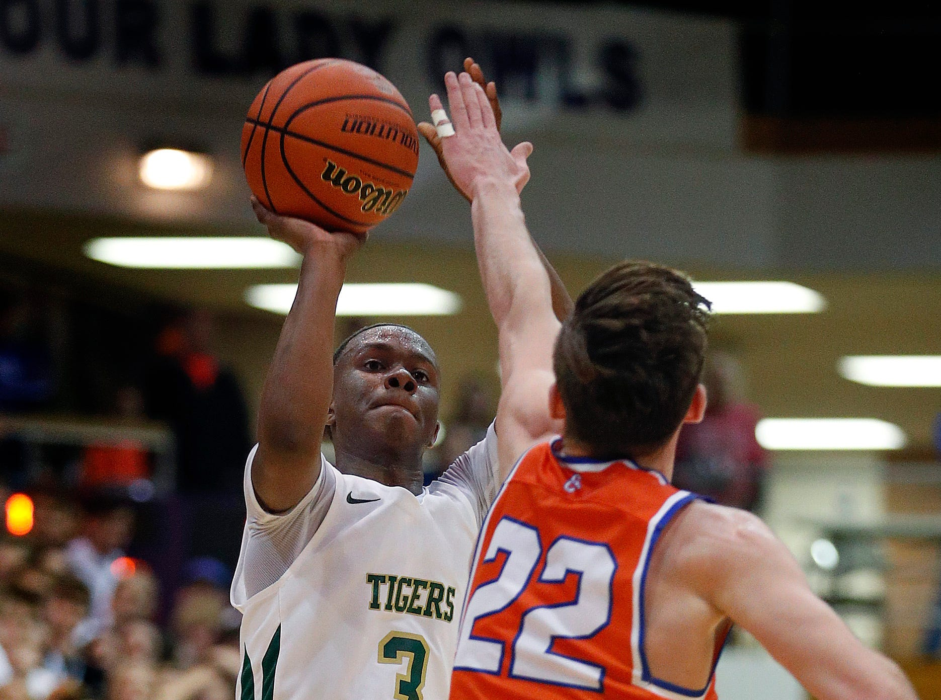 Crispus Attucks Tigers SinCere McMahon (3) puts up a three-point shot over Silver Creek Dragons Ty Kessinger (22) in the second half of their IHSAA boys' Semi-State basketball game at Seymour High School gym in Seymour IN, on Saturday, Mar. 16, 2019. The Silver Creek Dragons defeated the Crispus Attucks Tigers 72-69.