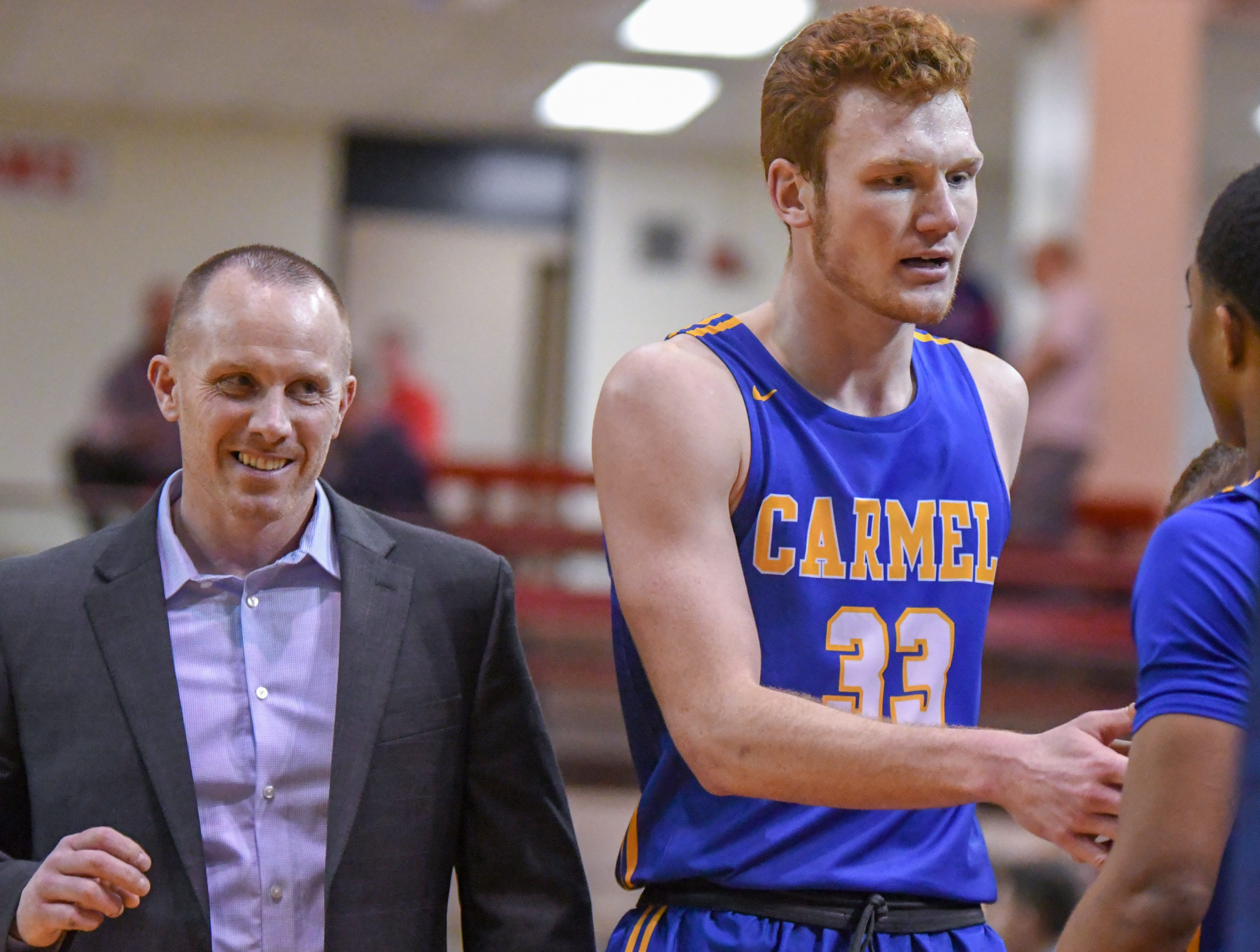 Carmel's John-Michael Mulloy leaves the game as coach Ryan Osborn smiles during his teams 71-42 win over Penn High School in Lafayette on Saturday March 16, 2019. Carmel moves on to the state finals after winning the 4A semi-state today.