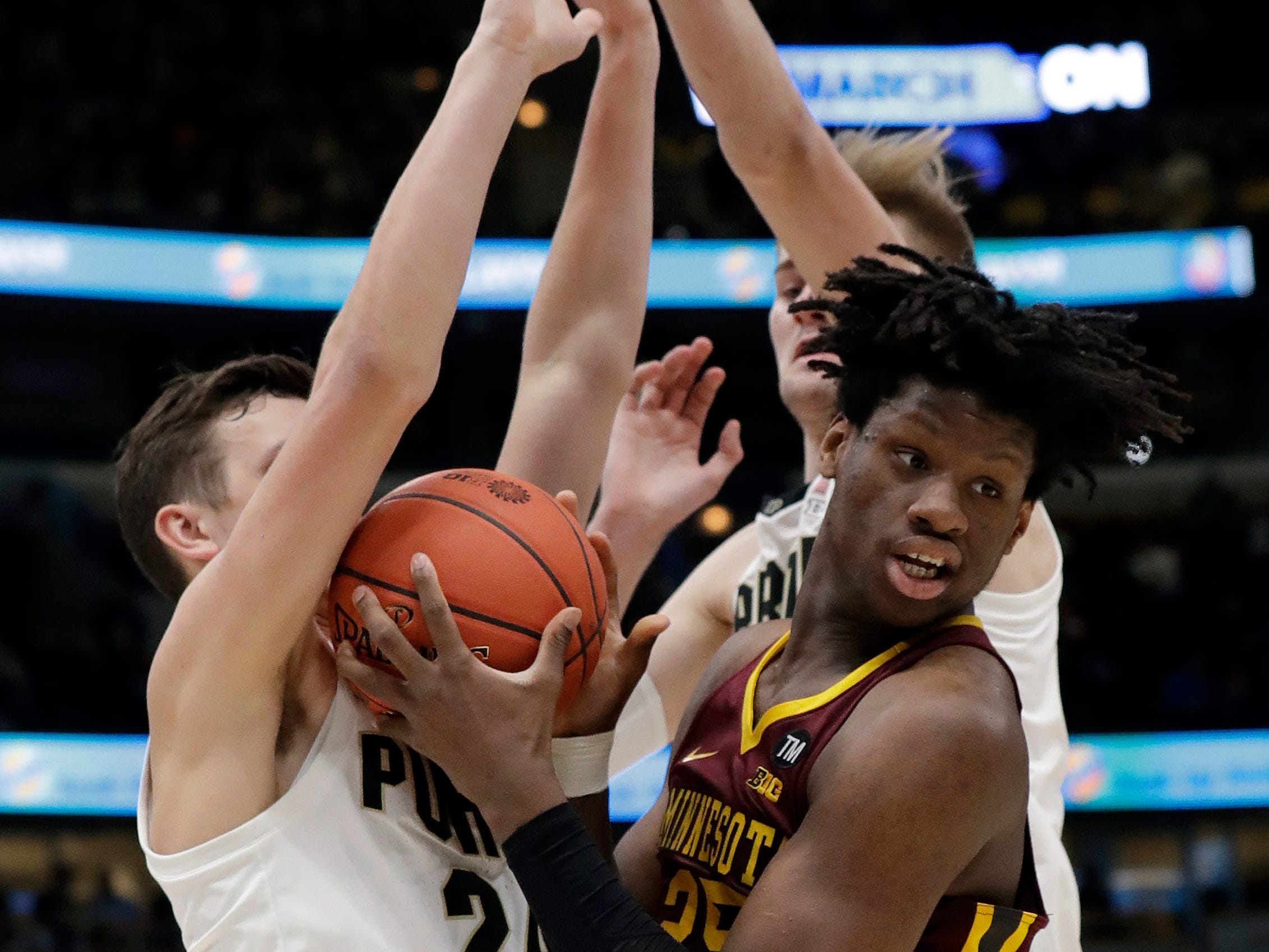 Minnesota's Daniel Oturu (25) battles for the possession of the ball against Purdue's Grady Eifert (24) and Matt Haarms during the first half of an NCAA college basketball game in the quarterfinals of the Big Ten Conference tournament, Friday, March 15, 2019, in Chicago. (AP Photo/Nam Y. Huh)