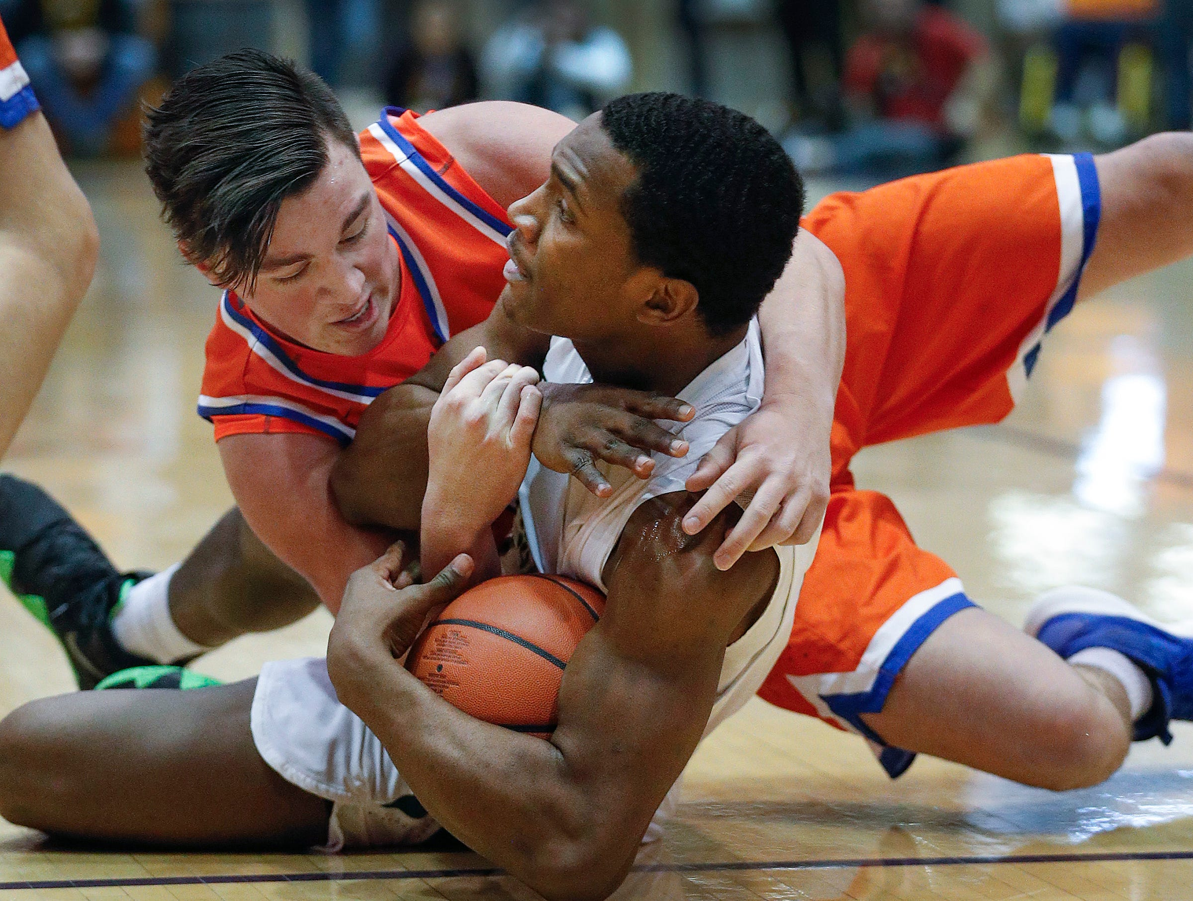 Crispus Attucks Tigers Jayon Barnett (12) and Silver Creek Dragons Joshua Landers (20)  scramble for a loose ball in the first half of their IHSAA boys' Semi-State basketball game at Seymour High School gym in Seymour IN, on Saturday, Mar. 16, 2019.