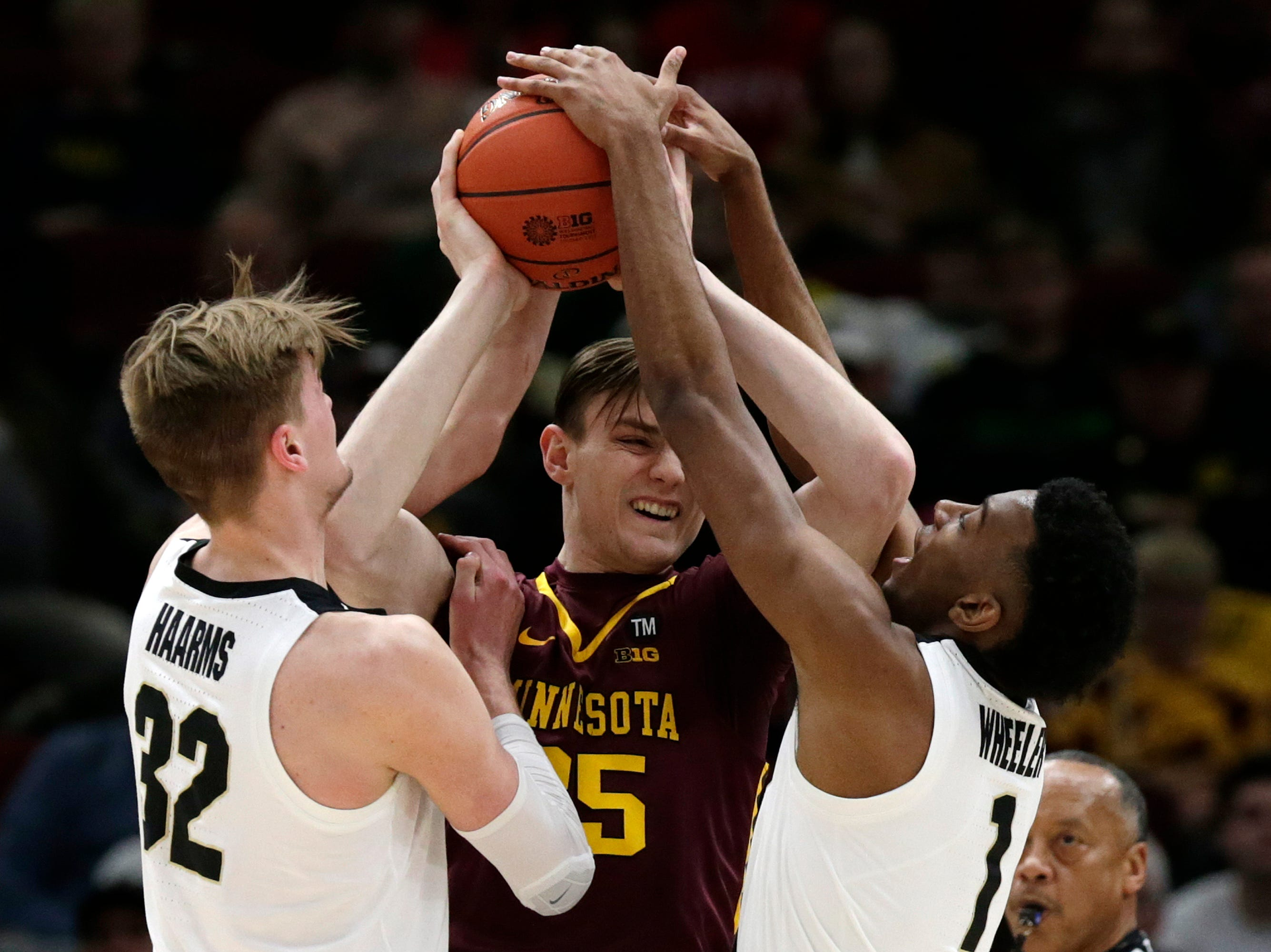 Minnesota's Matz Stockman (35) battles against Purdue's Matt Haarms (32) and Aaron Wheeler (1) as he tries to pass during the first half of an NCAA college basketball game in the quarterfinals of the Big Ten Conference tournament, Friday, March 15, 2019, in Chicago. (AP Photo/Kiichiro Sato)