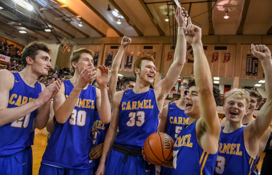 Carmel team members celebrate their 71-42 4A semi-state win over Penn High School in Lafayette on Saturday March 16, 2019.