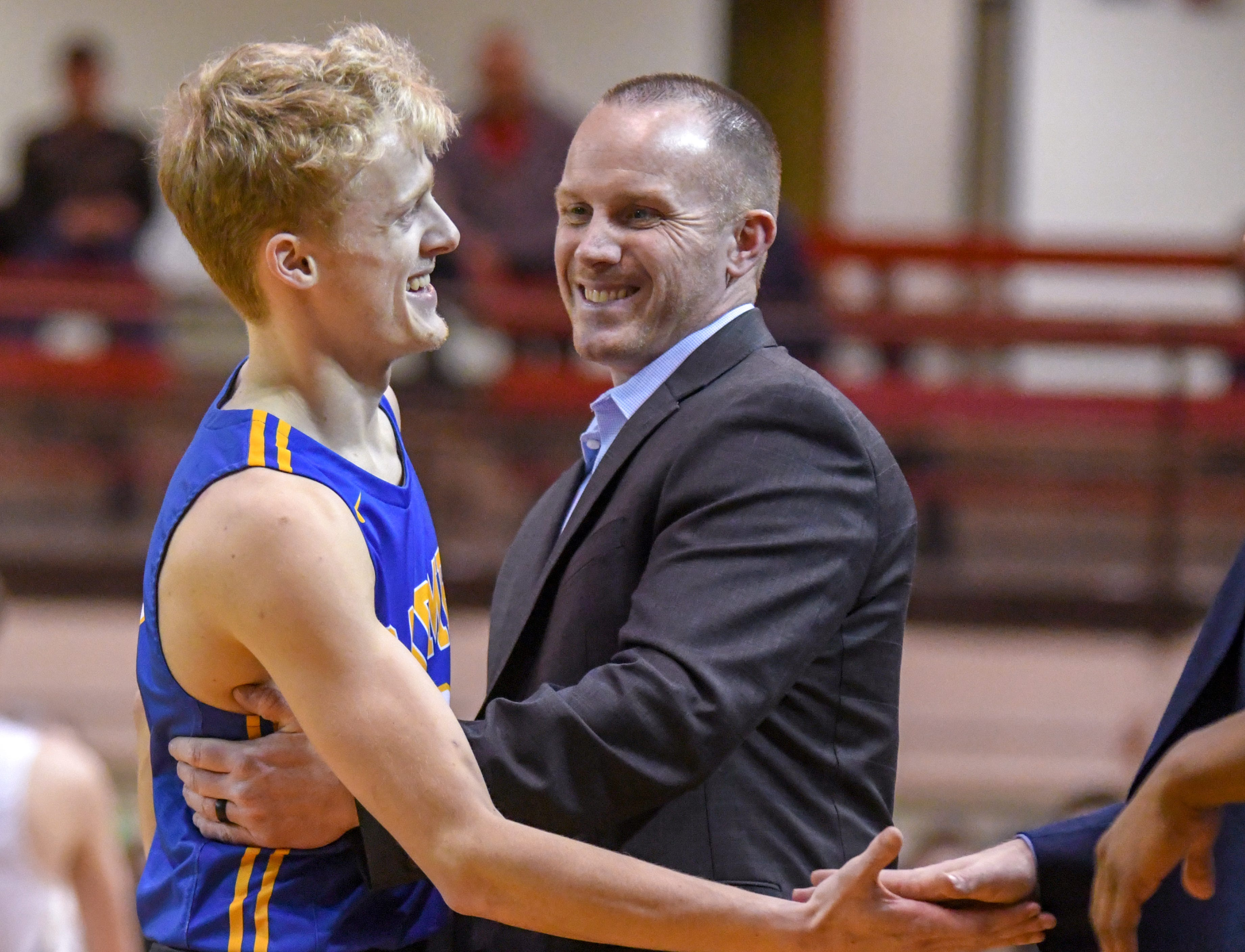 Carmel's Karsten Windlan hugs his coach Ryan Osborn near the end of the Greyhounds 71-42 win over Penn High School in Lafayette on Saturday March 16, 2019. Carmel moves on to the state finals after winning the 4A semi-state today.