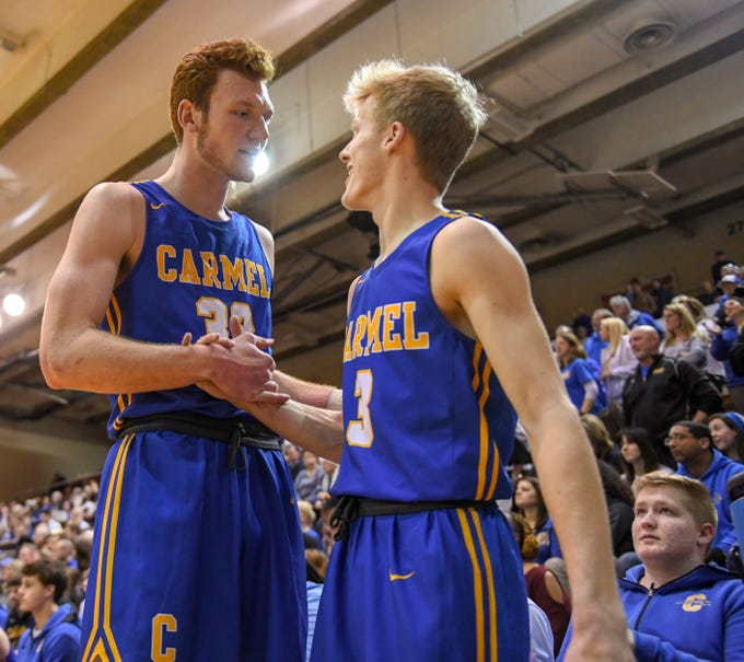 Carmel's John-Michael Mulloy, left, and Karsten Windlan shake hands following a 71-42 win over Penn High School in Lafayette on Saturday March 16, 2019. Carmel moves on to the state finals after winning the 4A semi-state today.