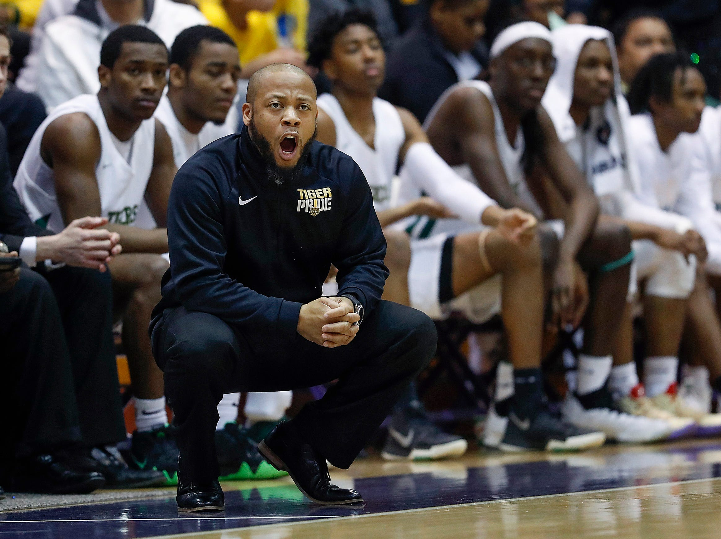 Crispus Attucks Tigers head coach Chris Hawkins calls out to his players in the first half of their IHSAA boys' Semi-State basketball game at Seymour High School gym in Seymour IN, on Saturday, Mar. 16, 2019.