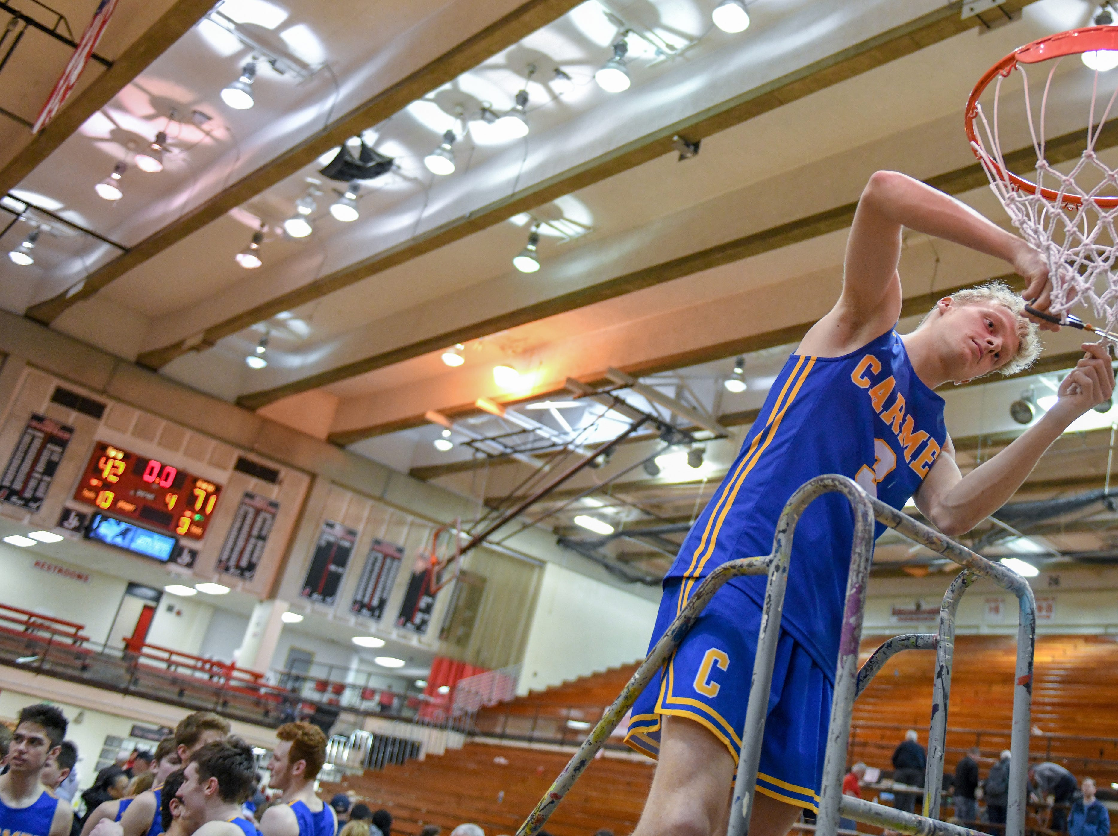 Carmel's Karsten Windlan cuts down the net after his teams 71-42 win over Penn High School in Lafayette on Saturday March 16, 2019. Carmel moves on to the state finals after winning the 4A semi-state today.