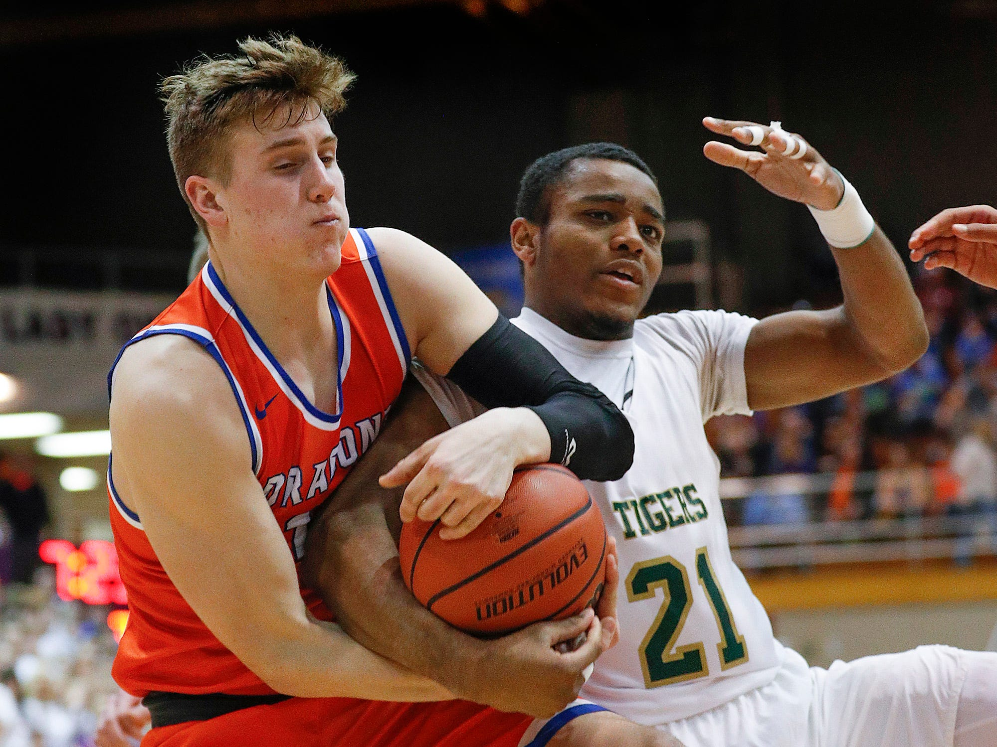 Silver Creek Dragons Jack Hawkins (14) and Crispus Attucks Tigers Courtney Radford (21) fight for a rebound in the second half of their IHSAA boys' Semi-State basketball game at Seymour High School gym in Seymour IN, on Saturday, Mar. 16, 2019. The Silver Creek Dragons defeated the Crispus Attucks Tigers 72-69.