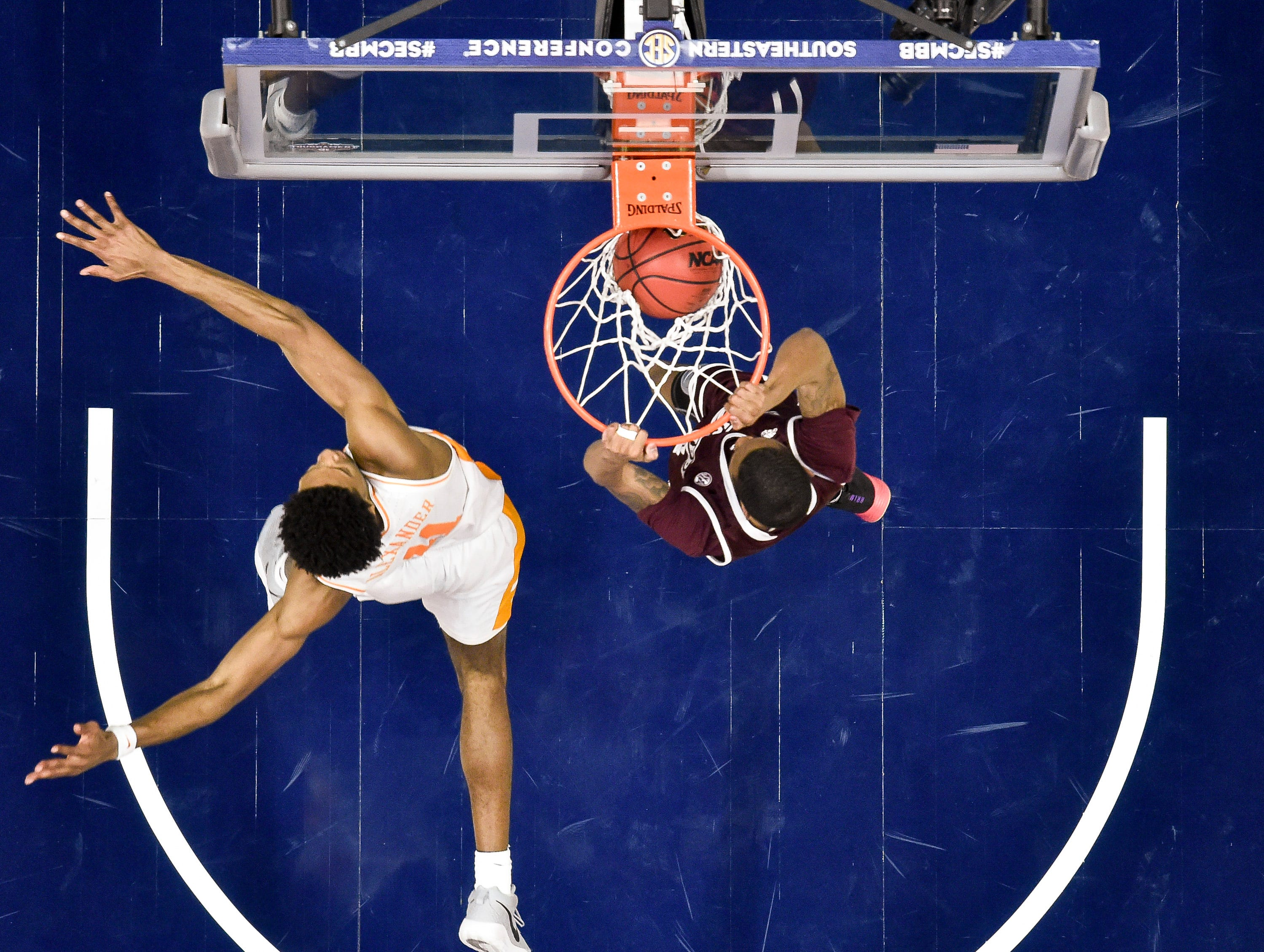 Mississippi State guard Tyson Carter (23) dunks past Tennessee forward Kyle Alexander (11) during the second half of the SEC Men's Basketball Tournament game at Bridgestone Arena in Nashville, Tenn., Friday, March 15, 2019.
