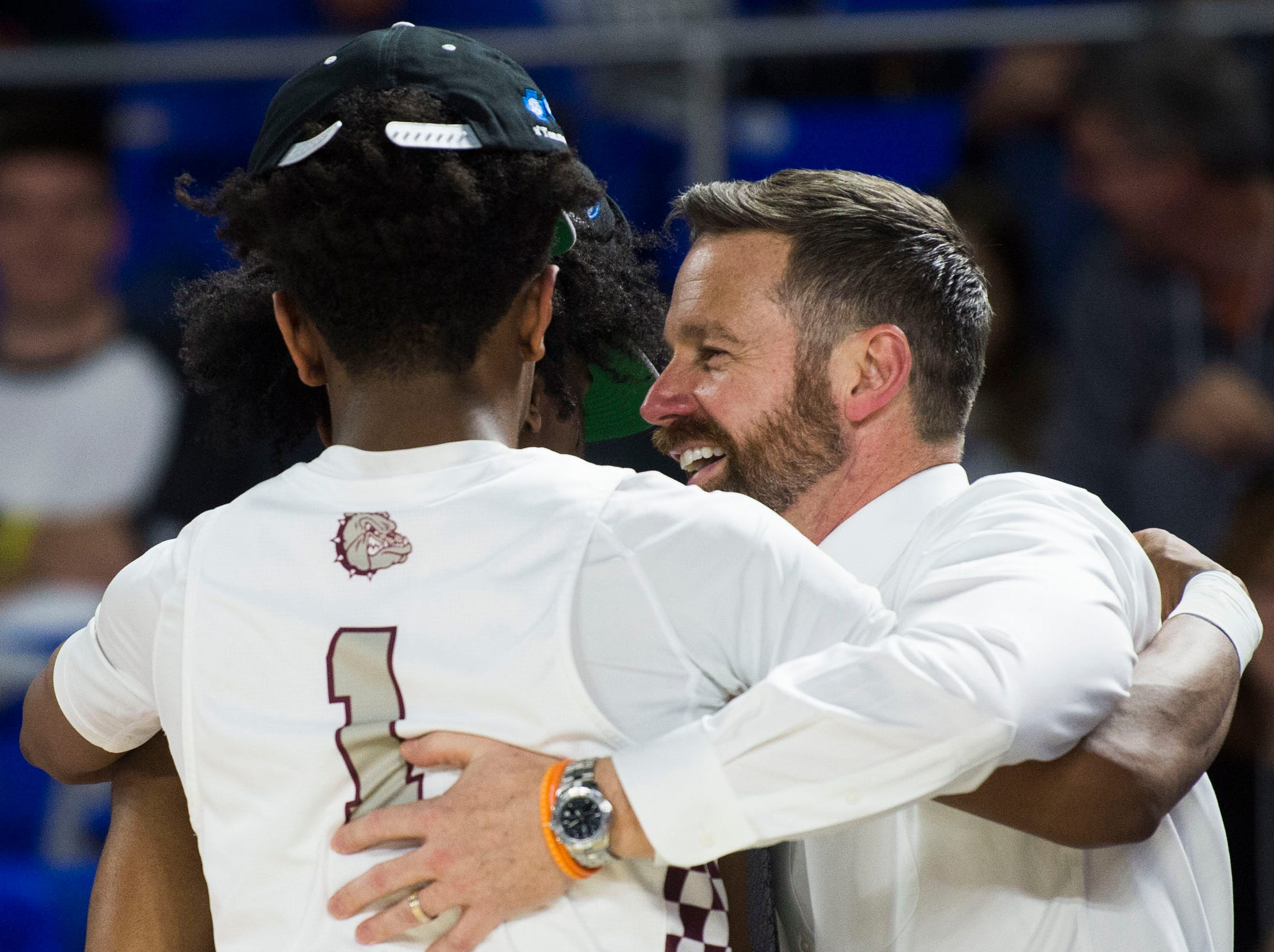 Bearden's head coach Jeremy Parrott hugs Bearden's Trent Stephney (1) and Bearden's Ques Glover (0) after a TSSAA AAA state championship game between Bearden and Memphis East at the Murphy Center in Murfreesboro, Saturday, March 16, 2019. Bearden defeated Memphis East 81-68.