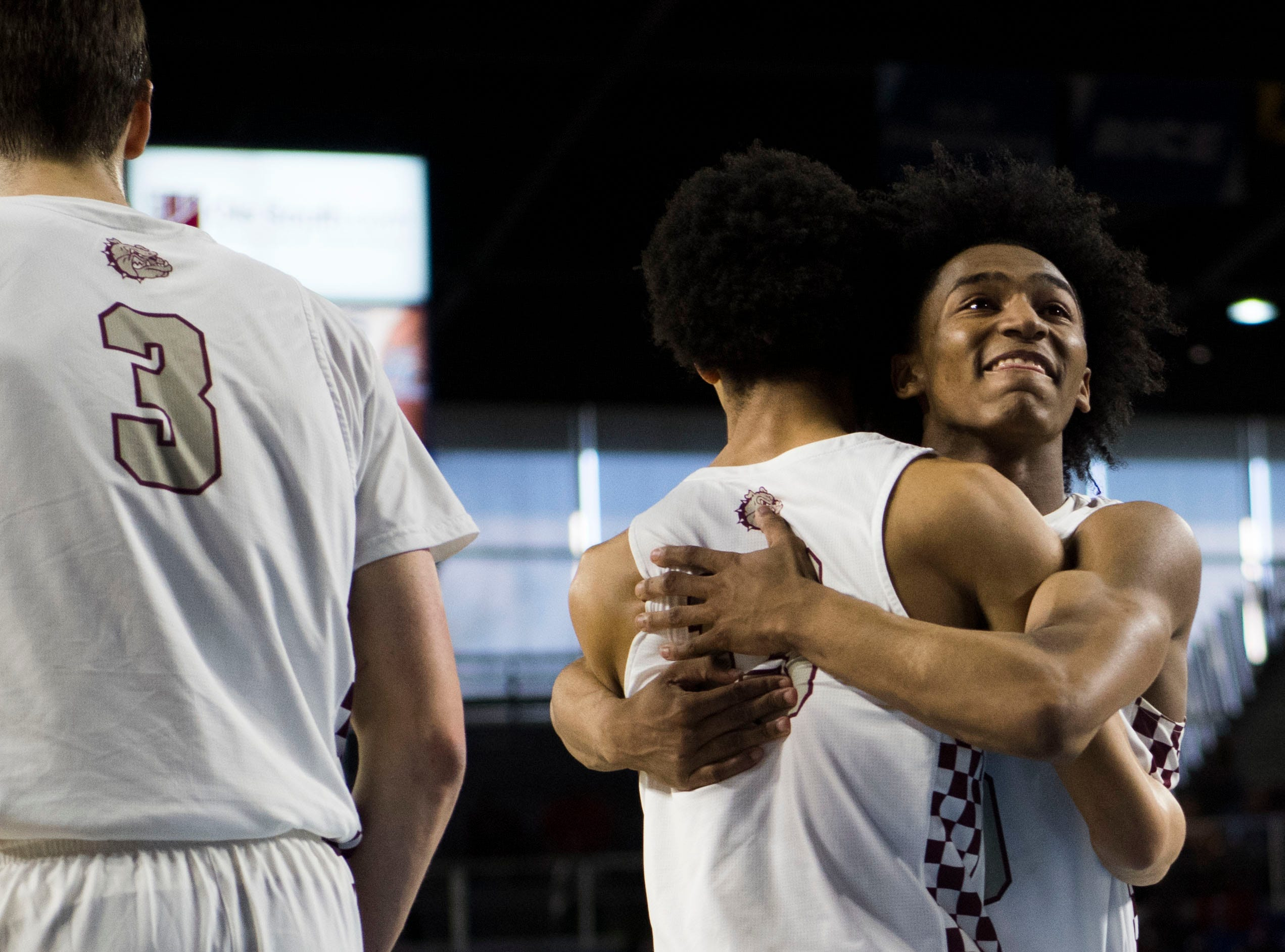 Bearden's Ques Glover (0) hugs Bearden's Roman Robinson (13) after a TSSAA AAA state championship game between Bearden and Memphis East at the Murphy Center in Murfreesboro, Saturday, March 16, 2019. Bearden defeated Memphis East 81-68.