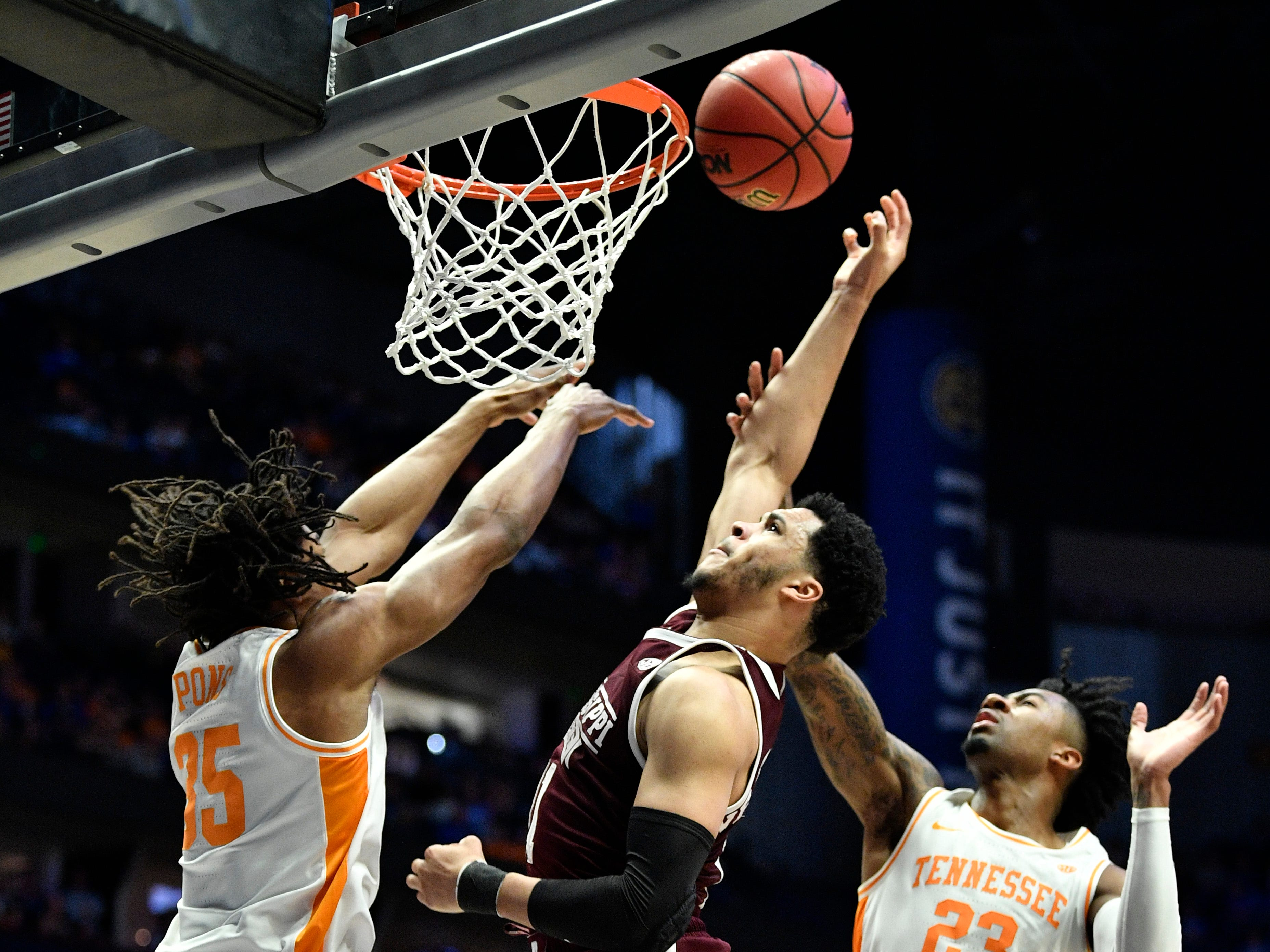 Mississippi State guard Quinndary Weatherspoon (11) goes up between Tennessee forward Yves Pons (35) and guard Jordan Bowden (23) during the second half of the SEC Men's Basketball Tournament game at Bridgestone Arena in Nashville, Tenn., Friday, March 15, 2019.