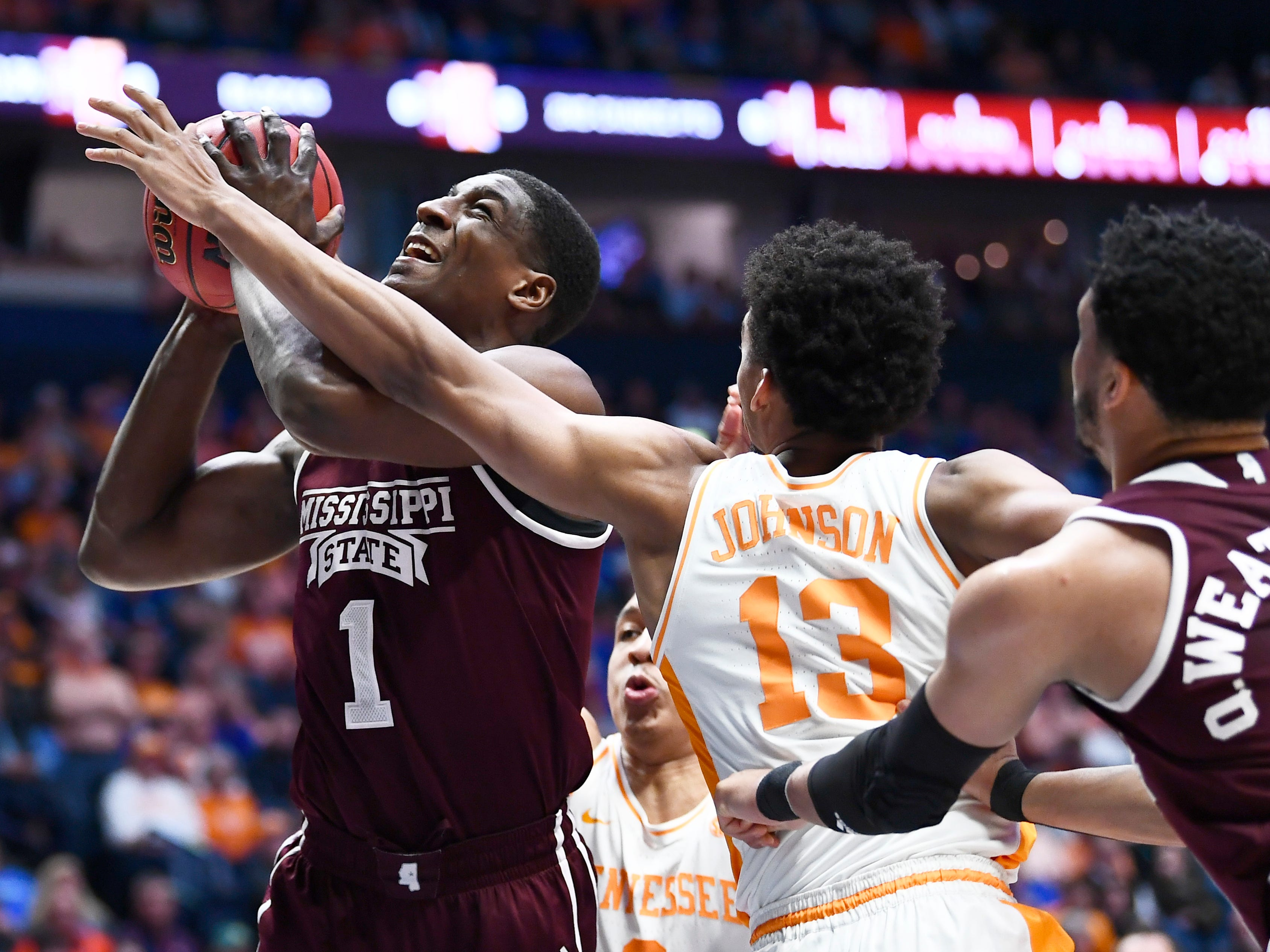 Mississippi State forward Reggie Perry (1) is fouled on the play while defended by Tennessee guards Admiral Schofield (5) and Jalen Johnson (13) during the first half of the SEC Men's Basketball Tournament game at Bridgestone Arena in Nashville, Tenn., Friday, March 15, 2019.
