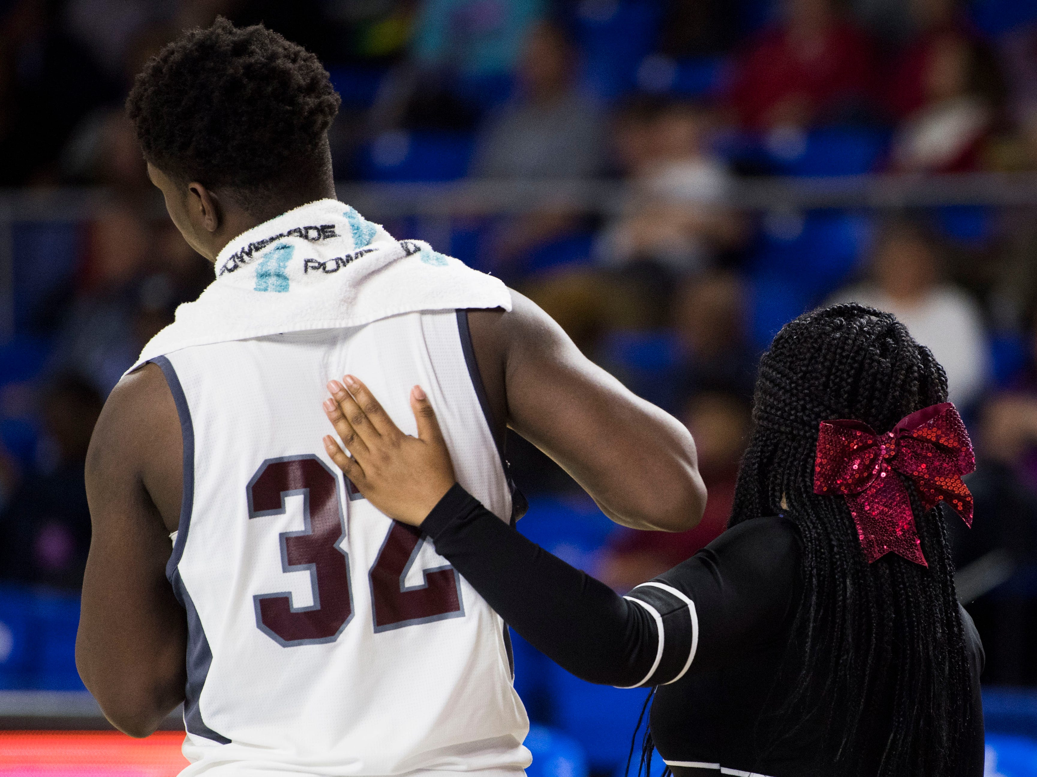 Fulton's Deshawn Page (32) is comforted by a cheerleader after a TSSAA AA state championship game between c