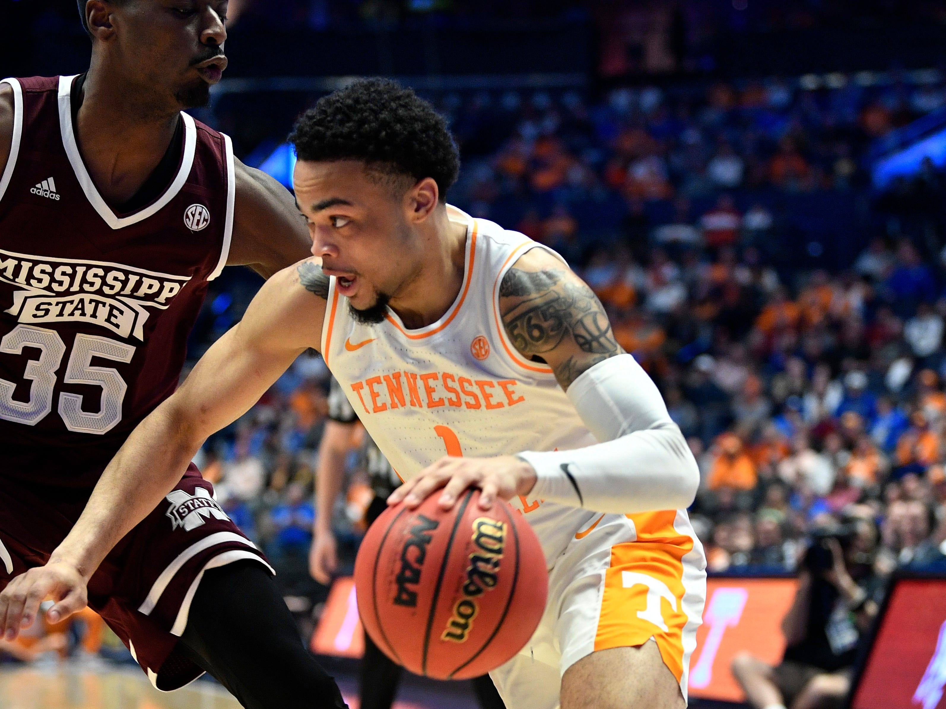 Tennessee guard Lamonte Turner (1) moves the ball defended by Mississippi State forward Aric Holman (35) during the first half of the SEC Men's Basketball Tournament game at Bridgestone Arena in Nashville, Tenn., Friday, March 15, 2019.