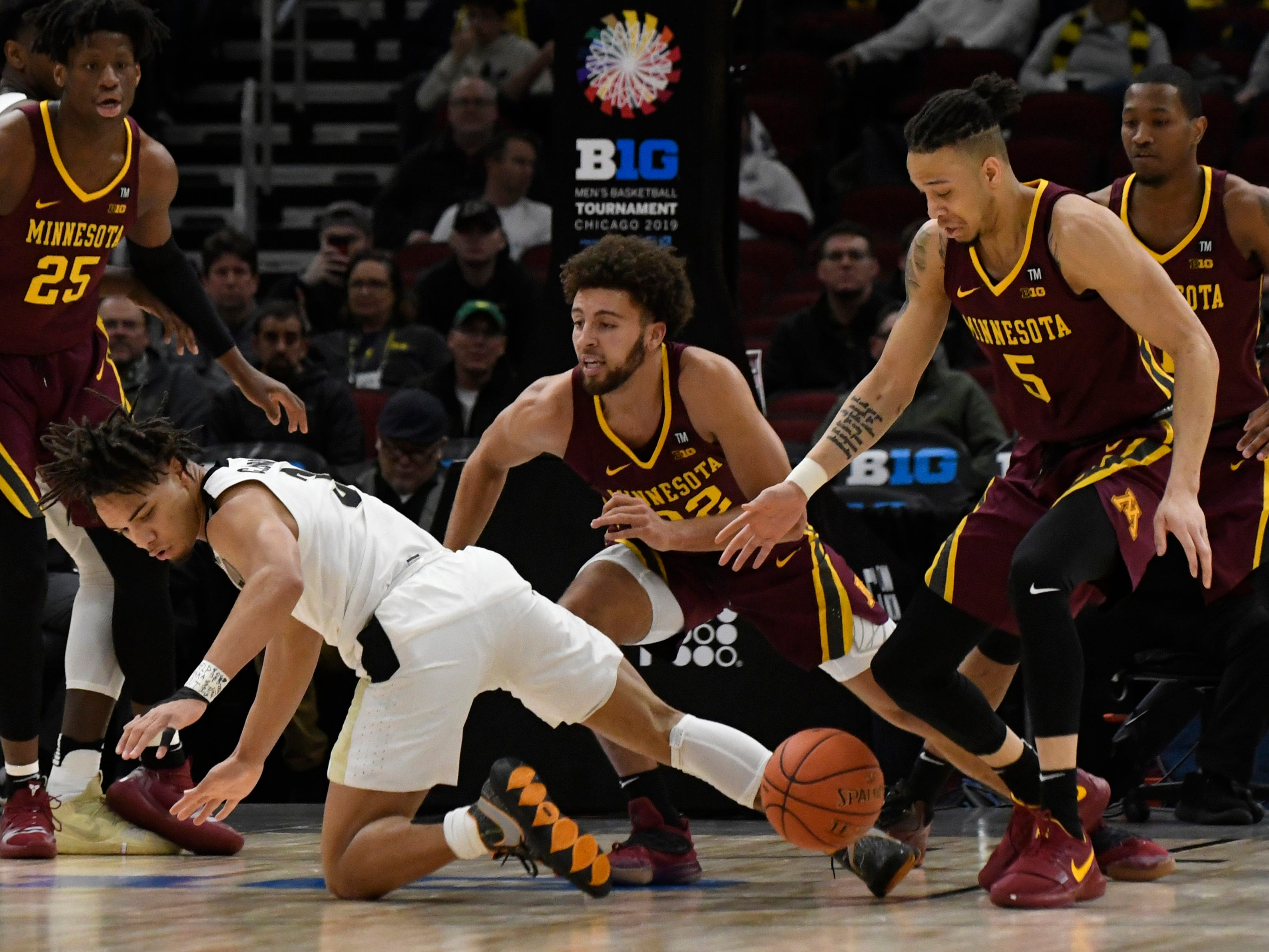 Mar 15, 2019; Chicago, IL, USA; Purdue Boilermakers guard Carsen Edwards (3) and Minnesota Golden Gophers guard Gabe Kalscheur (22) and guard Amir Coffey (5) chase a loose ball during the first half in the Big Ten conference tournament at United Center. Mandatory Credit: David Banks-USA TODAY Sports