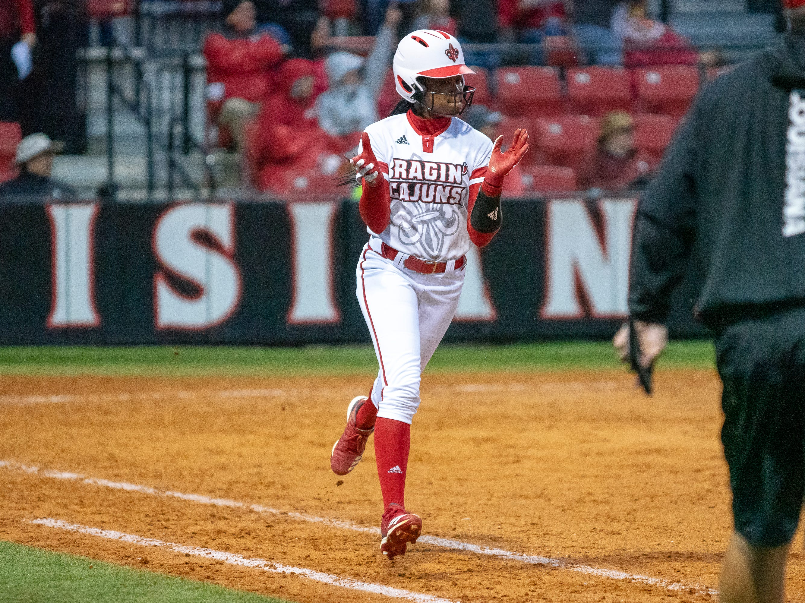 UL's Raina O'Neal celebrates her home run while jogging to first base as the Ragin' Cajuns take on the Troy Trojans at Lamson Park, Yvette Girouard Field on Friday, March 15, 2019.