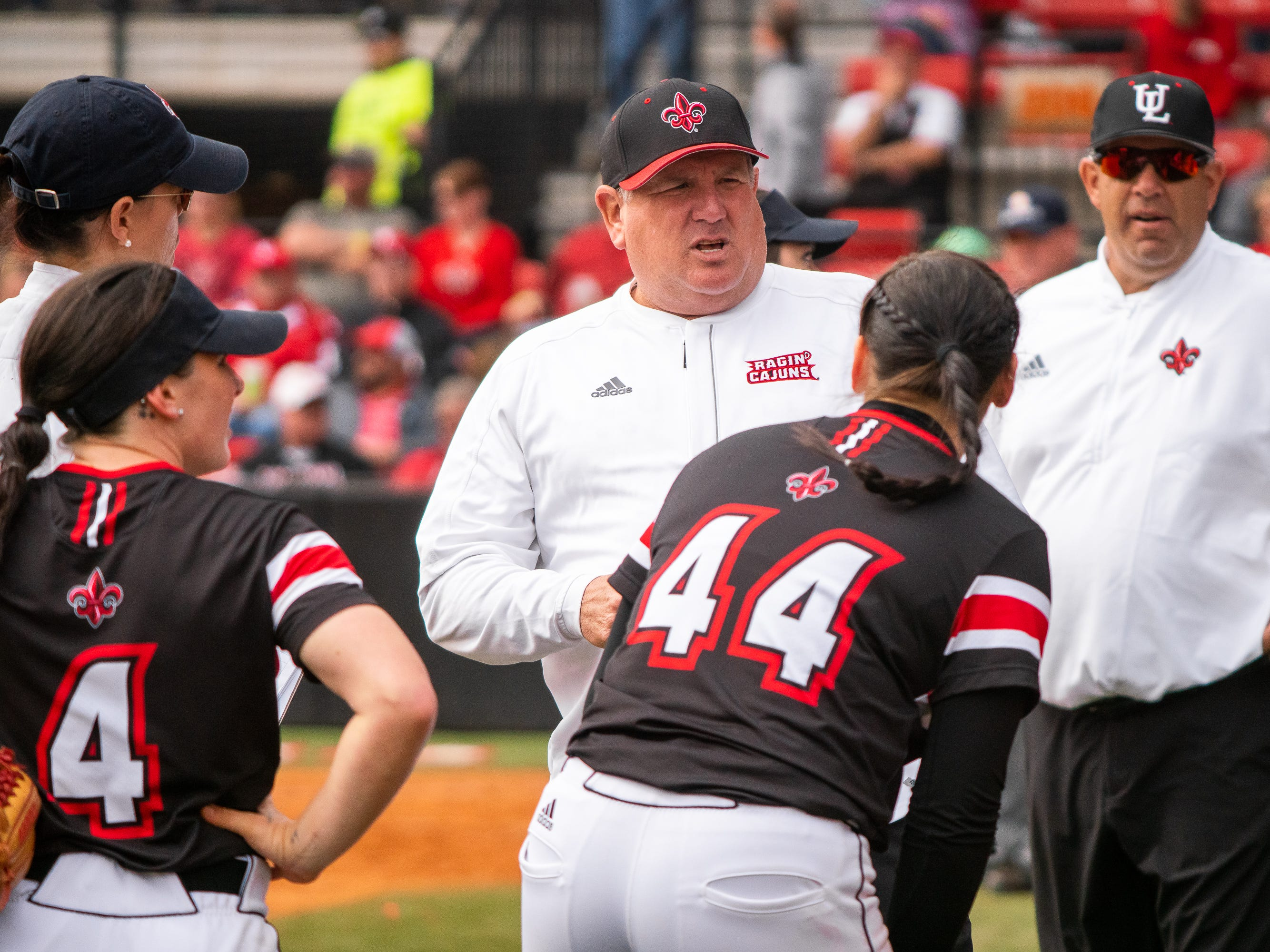 UL's head softball coach Gerry Glasco talks to his players in between innings as the Ragin' Cajuns take on the Troy Trojans at Yvette Girouard Field at Lamson Park on Saturday, March 16, 2019.