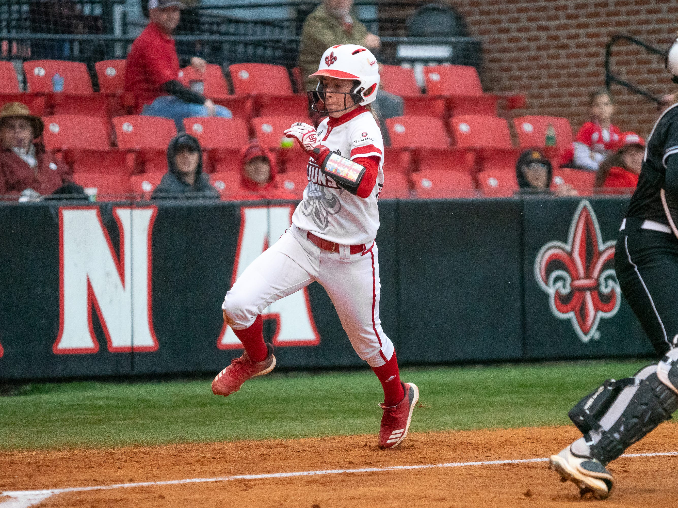 UL's Kara Gremillion runs behind the catcher to score a run for her team as the Ragin' Cajuns take on the Troy Trojans at Lamson Park, Yvette Girouard Field on Friday, March 15, 2019.