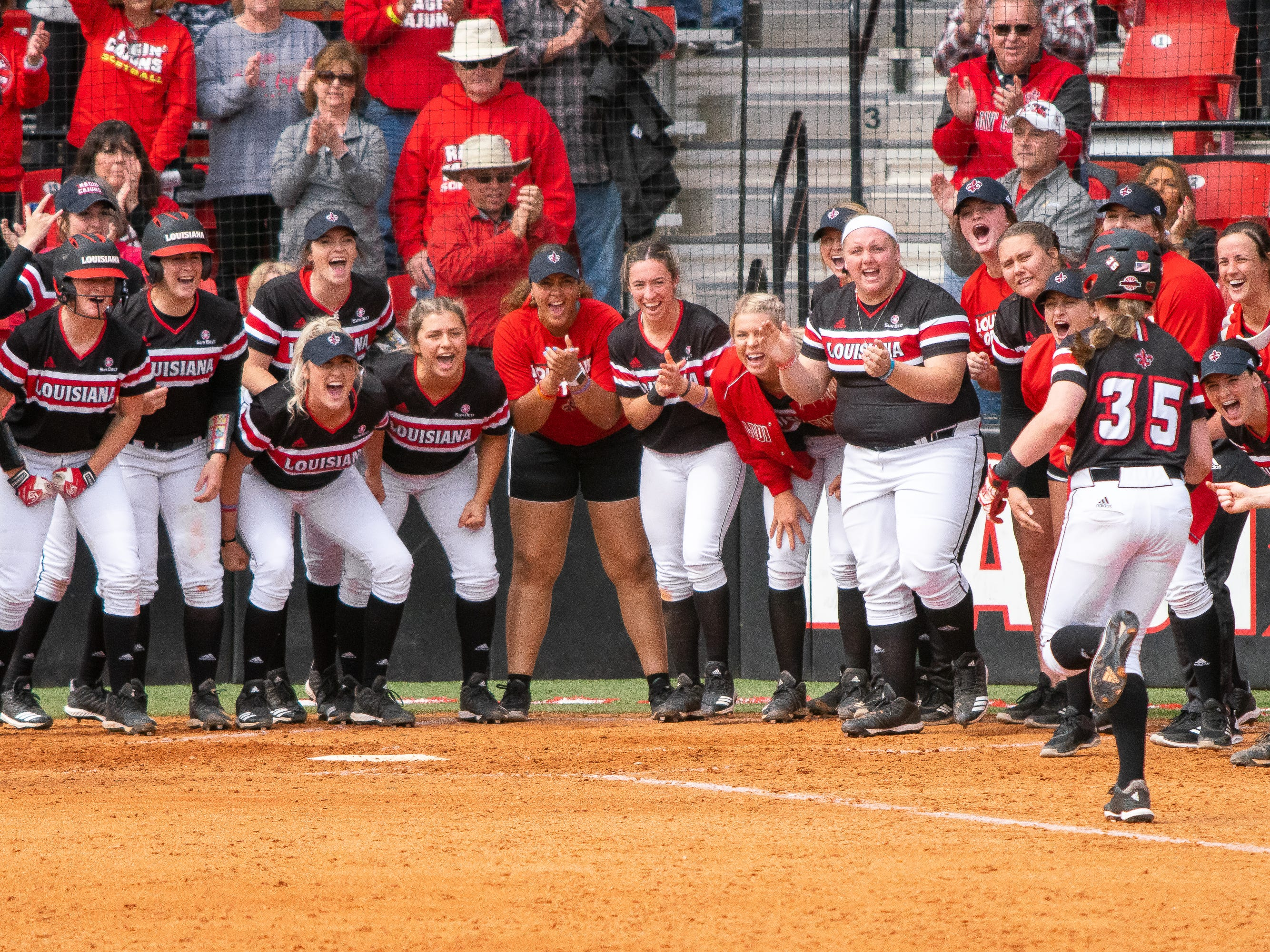 The UL softball team gathers around home plate to welcome Sarah Hudek after her home run hit as the Ragin' Cajuns take on the Troy Trojans at Yvette Girouard Field at Lamson Park on Saturday, March 16, 2019.