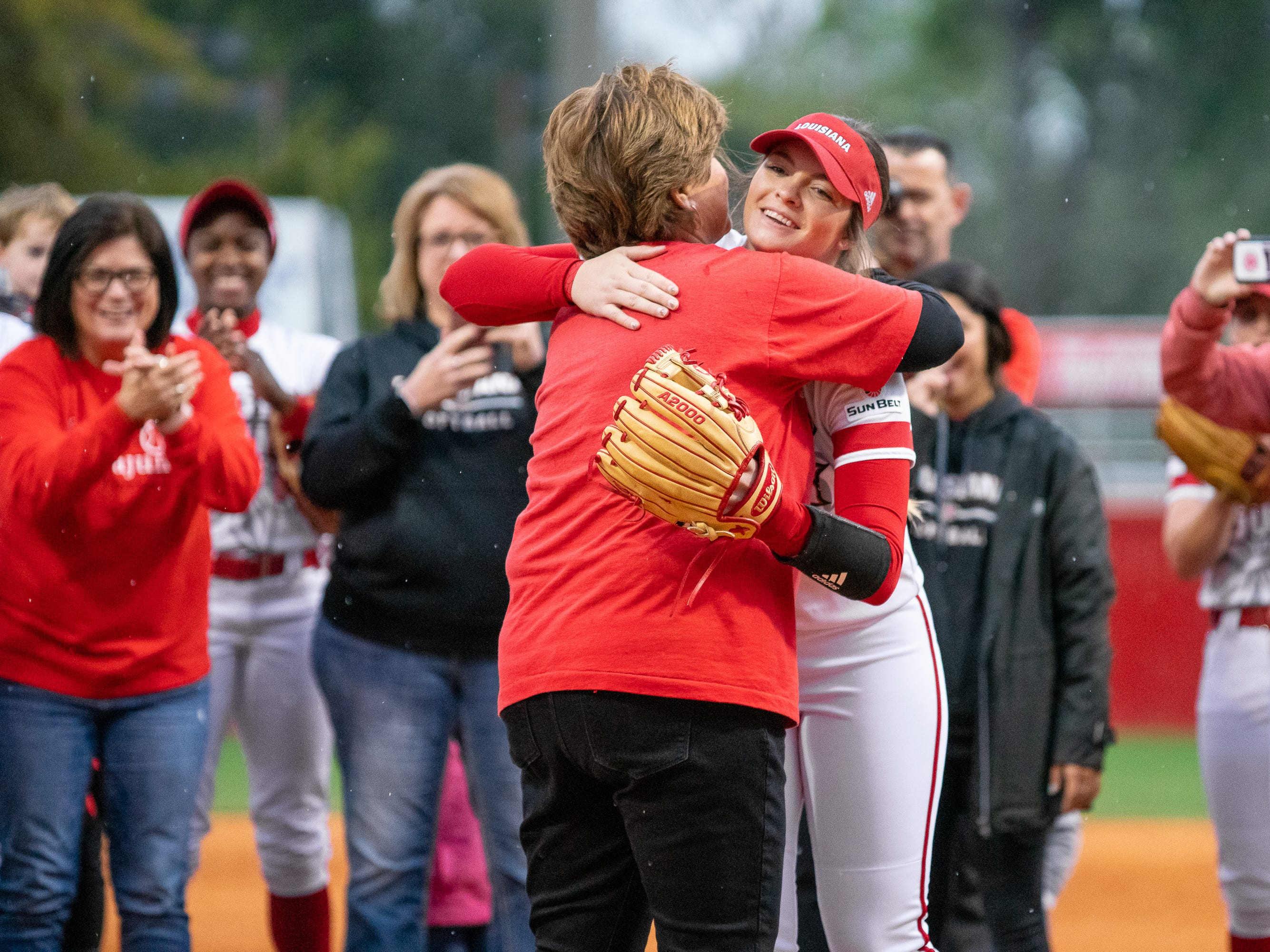 Former UL softball coach Yvette Girouard embraces Summer Ellyson after the first pitch as the Ragin' Cajuns take on the Troy Trojans at Lamson Park, Yvette Girouard Field on Friday, March 15, 2019.
