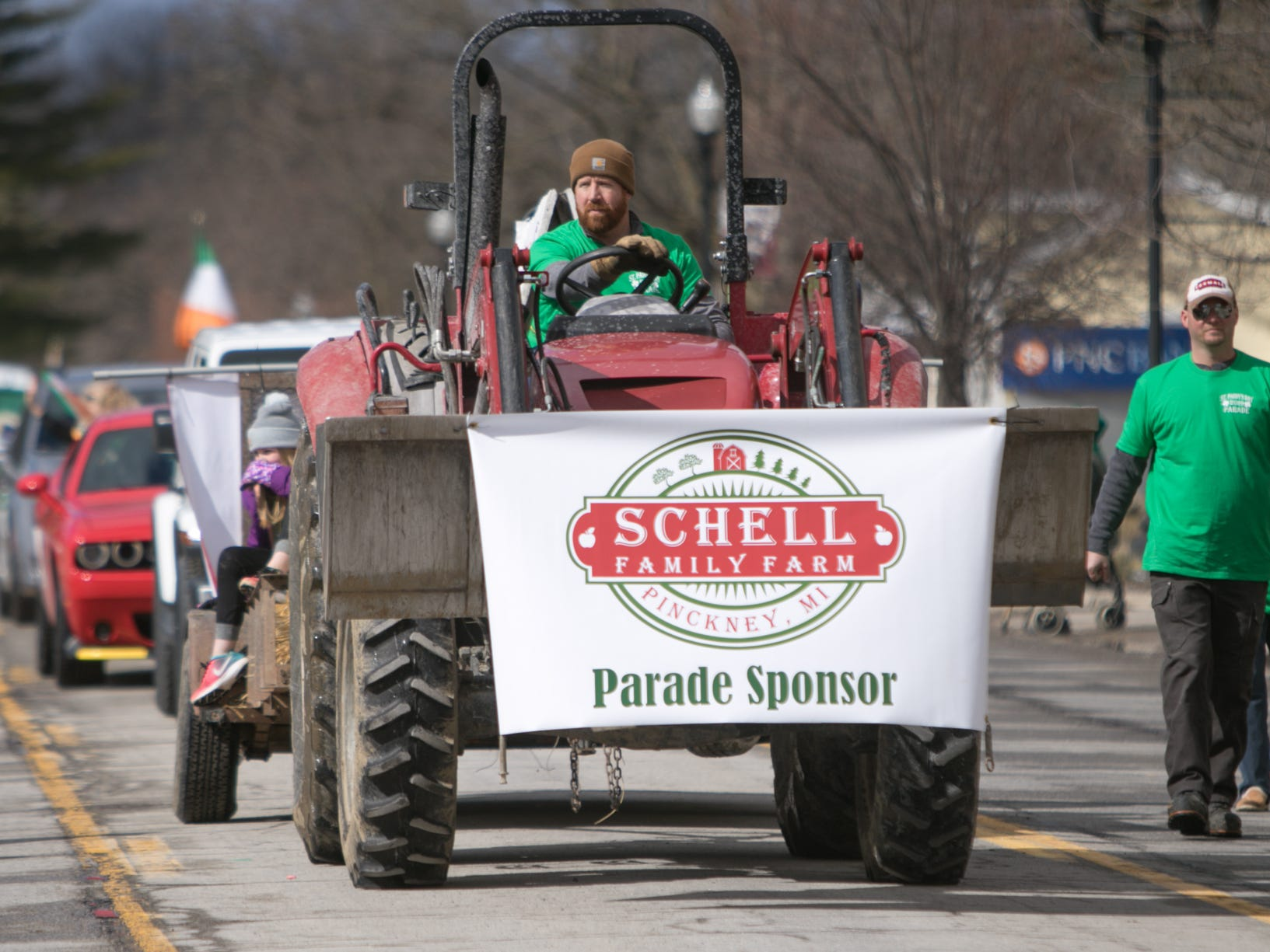 The Schell Family Farm, accompanied by members of the Pinckney High School baseball program, head down the St. Patrick's Day parade route Saturday, March 16, 2019.