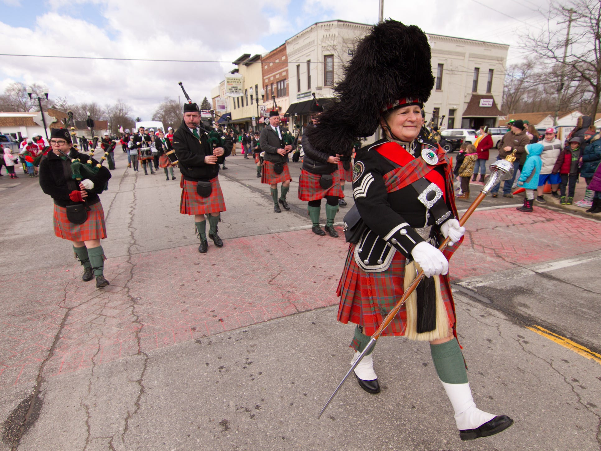Christy Haradean, a member of the honor guard of the Michigan Scottish Pipes and Drums band, leads the group in the St. Patrick's Day parade Saturday, March 16, 2019.