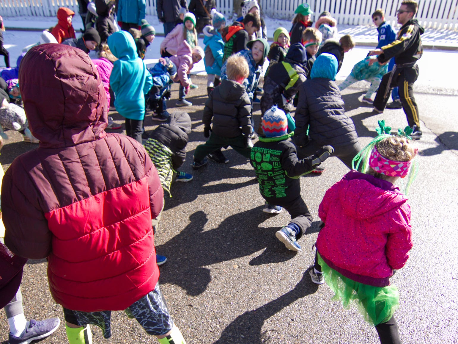 Young runners stretch in preparation for the Kids' Fun Run Saturday, March 16, 2019, before the St. Patrick's Day parade.