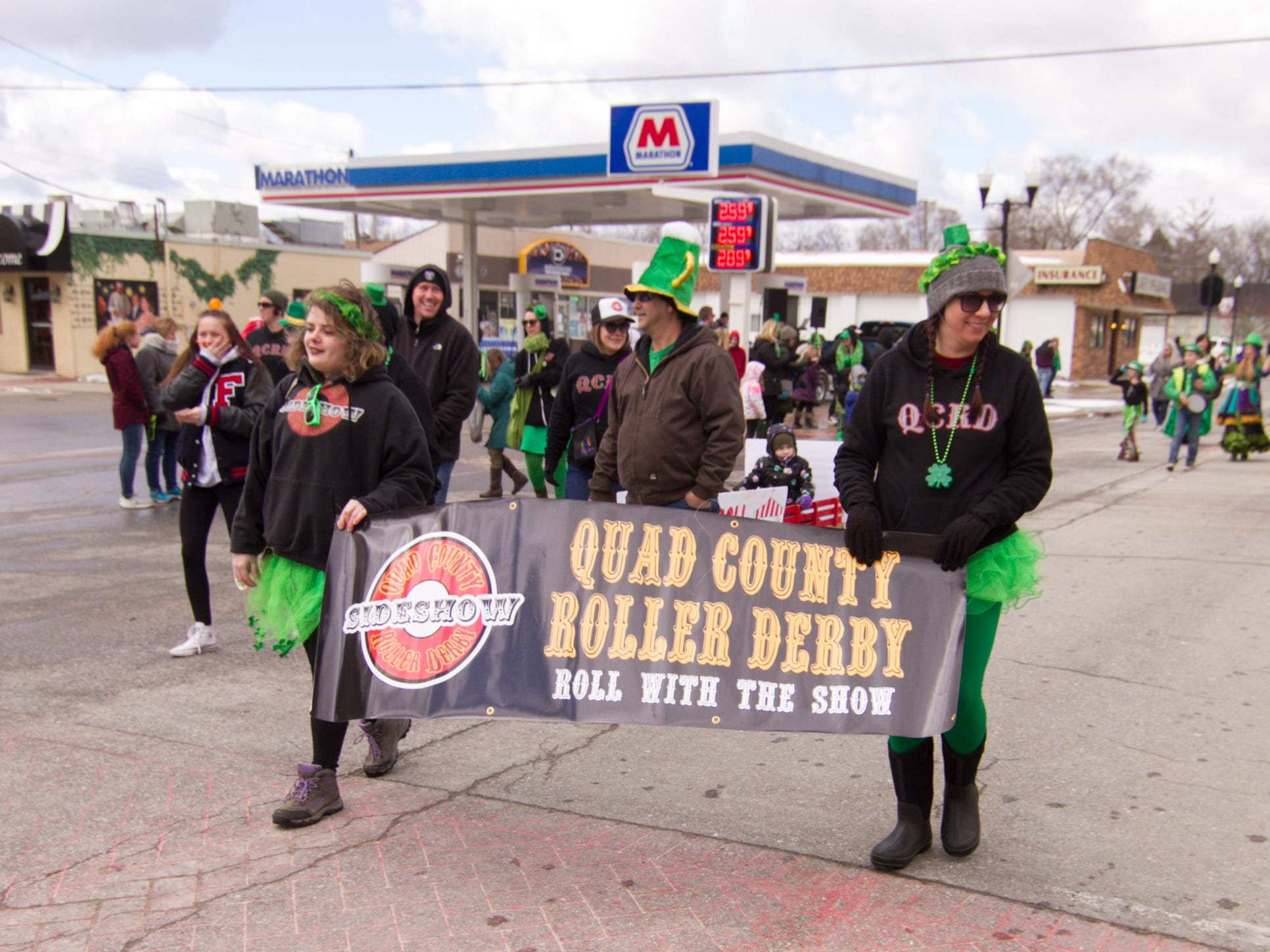 Members of the Quad County Roller Derby walk in the Pinckney St. Patrick's Day parade Saturday, March 16, 2019.