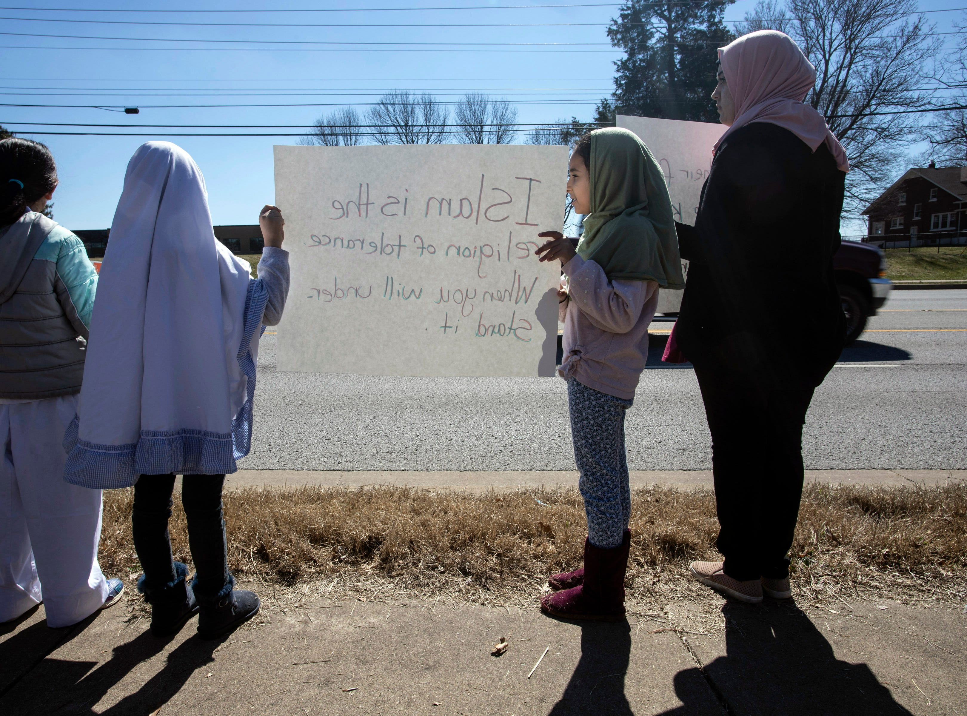 Some of the youngest members of the Louisville Muslim community hoisted handmade signs for passing traffic along Westport Road on Saturday afternoon before attending a prayer service to honor the victims of Friday's mass shooting in a New Zealand mosque. 3/16/19