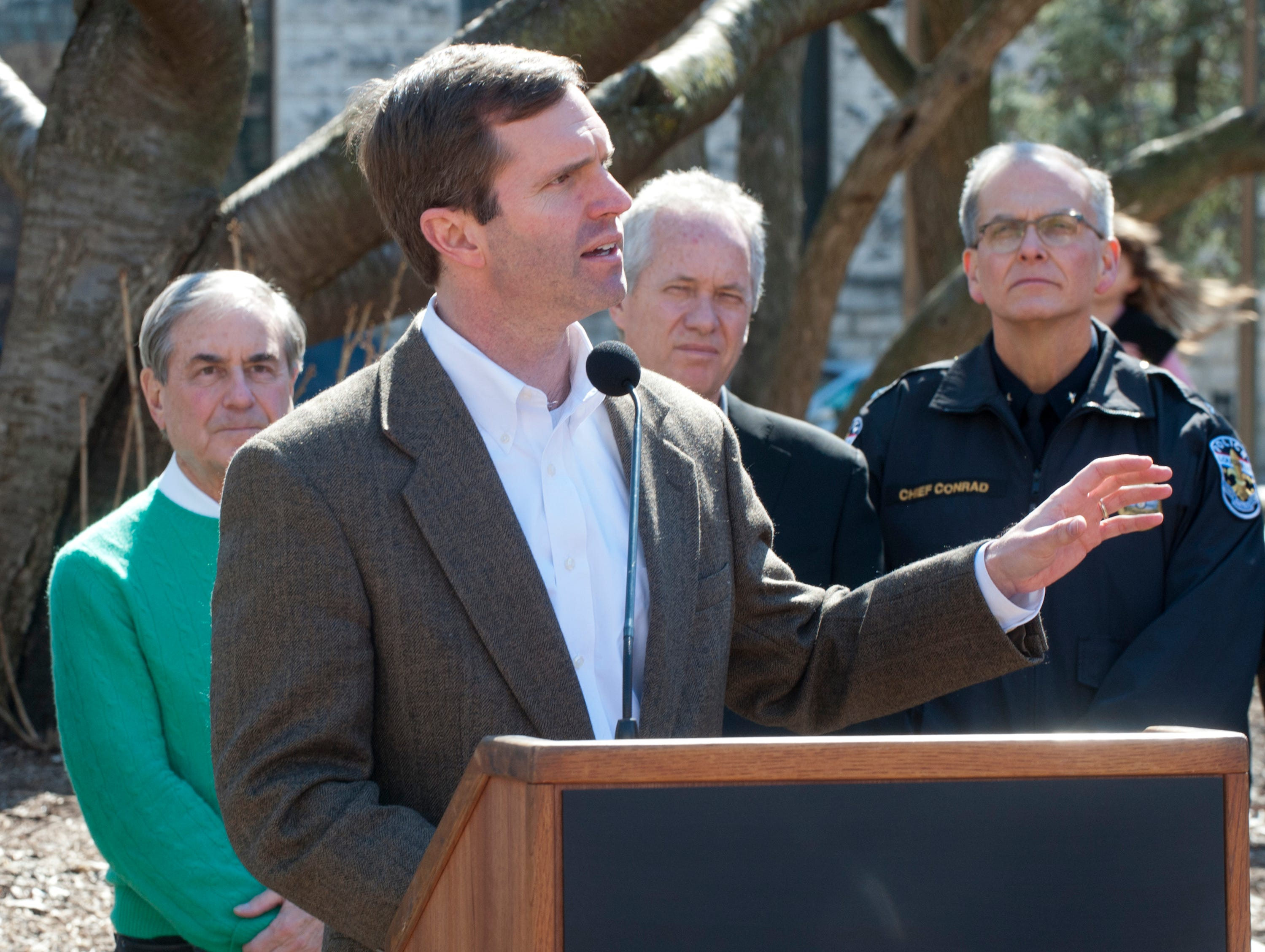 Kentucky State Attorney General Andy Beshear speaks at the vigil. Behind him, (l-r), are U.S. Representative John Yarmuth (D-Louisville,) Louisville Metro Mayor Greg Fischer and Louisville Metro Police Chief Steve Conrad. 16 March 2019